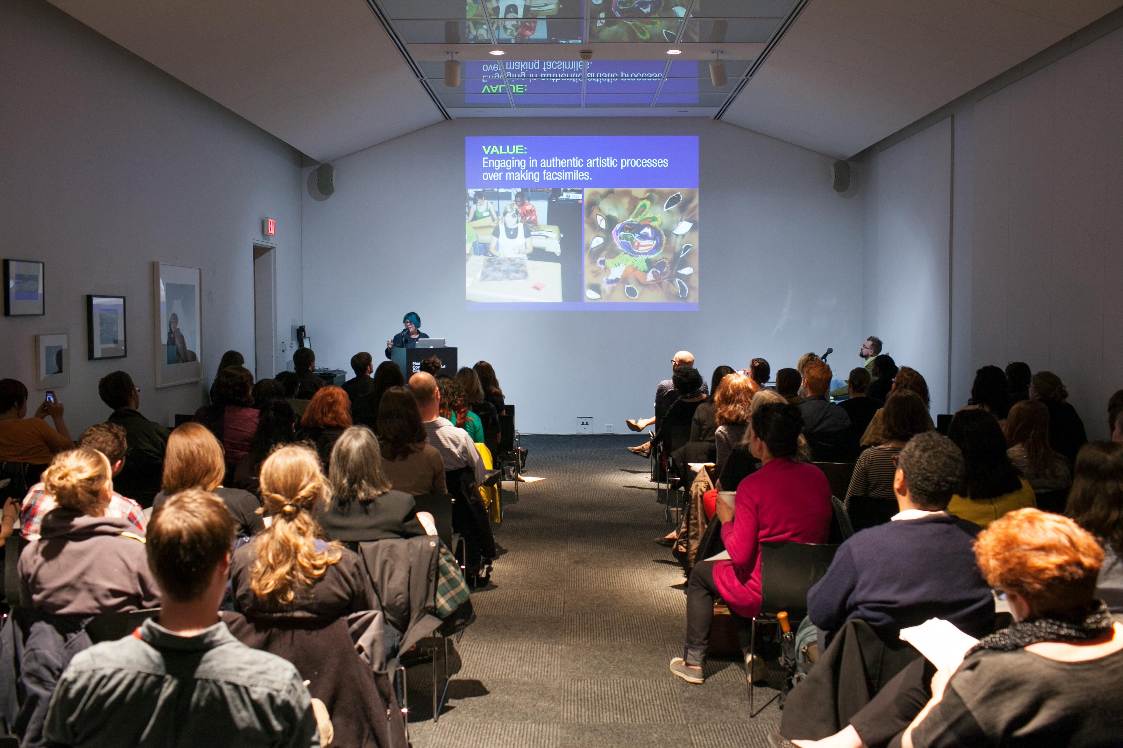 A room is full of people sitting in rows of chairs, taking notes, and looking up at a projection of a presentation, while someone speaks at the front podium.