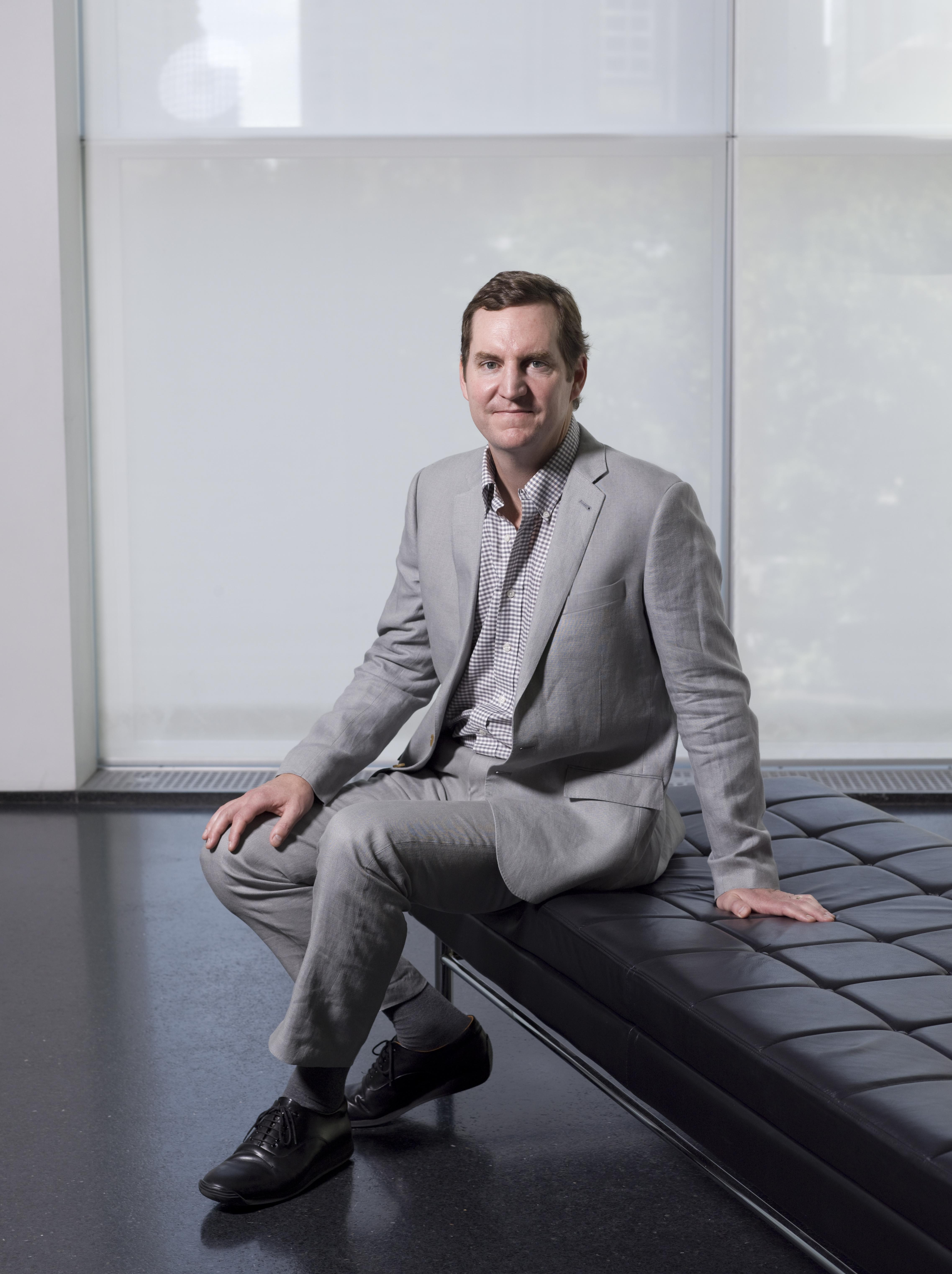 A tall, dark-haired, clean-shaven white man wearing a grey suit and gingham checkered shirt sits on a black leather bench in the MCA's lobby.
