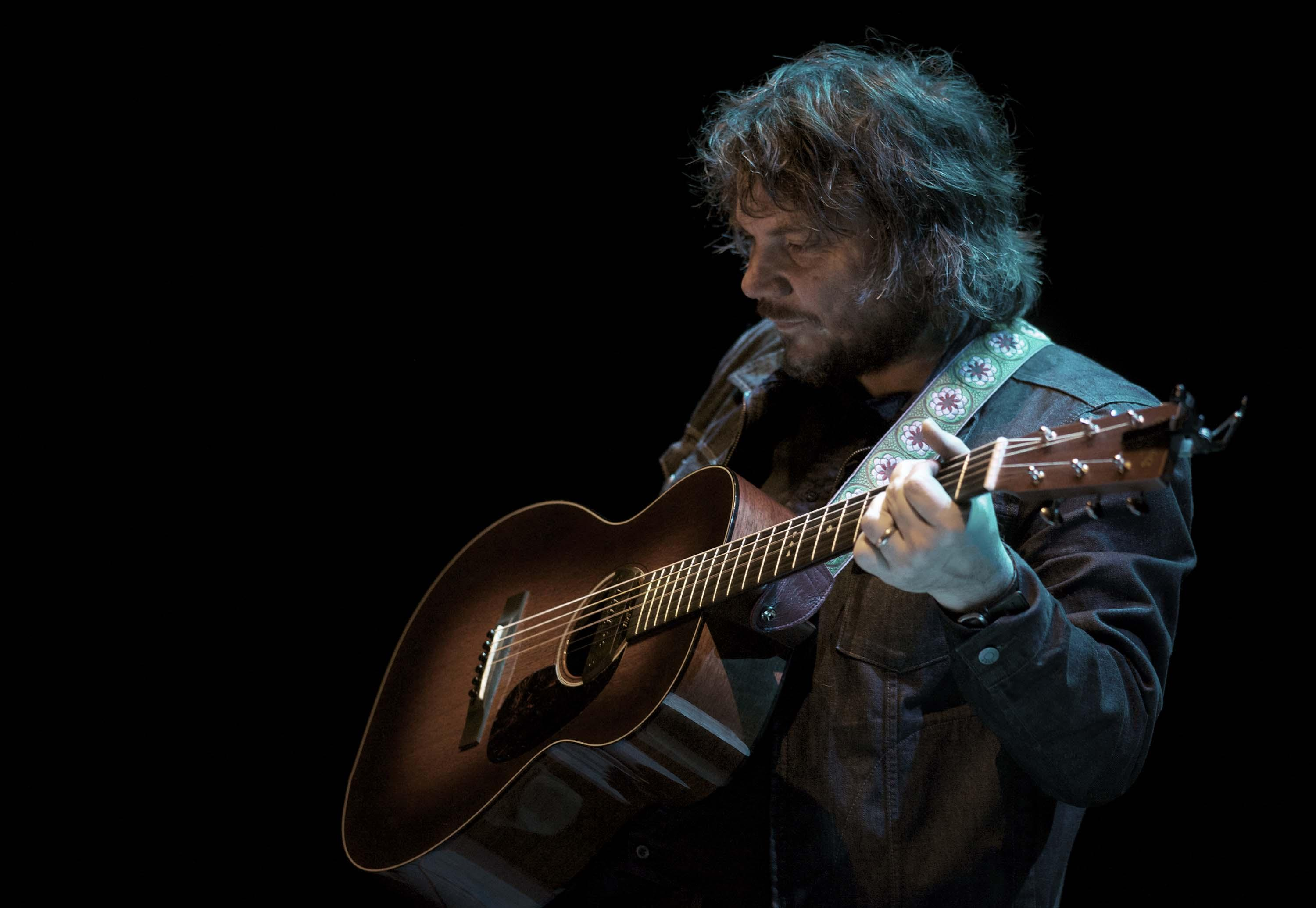 A man with long shaggy hair wearing a black denim jacket holds a wooden acoustic guitar.