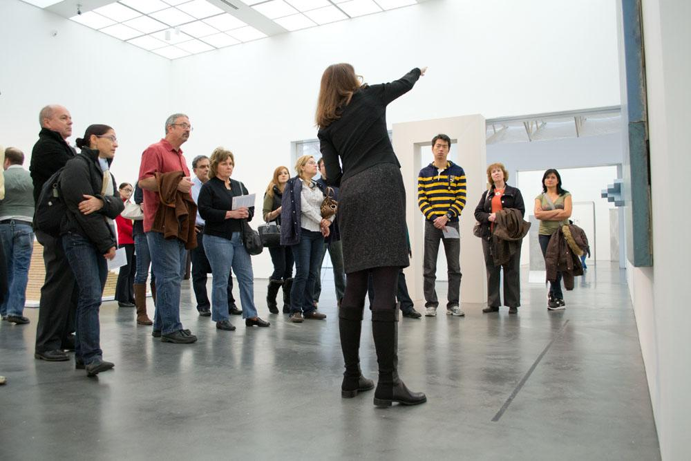 A woman points out a detail in an artwork as a group of people surround her listening and looking at the artwork.