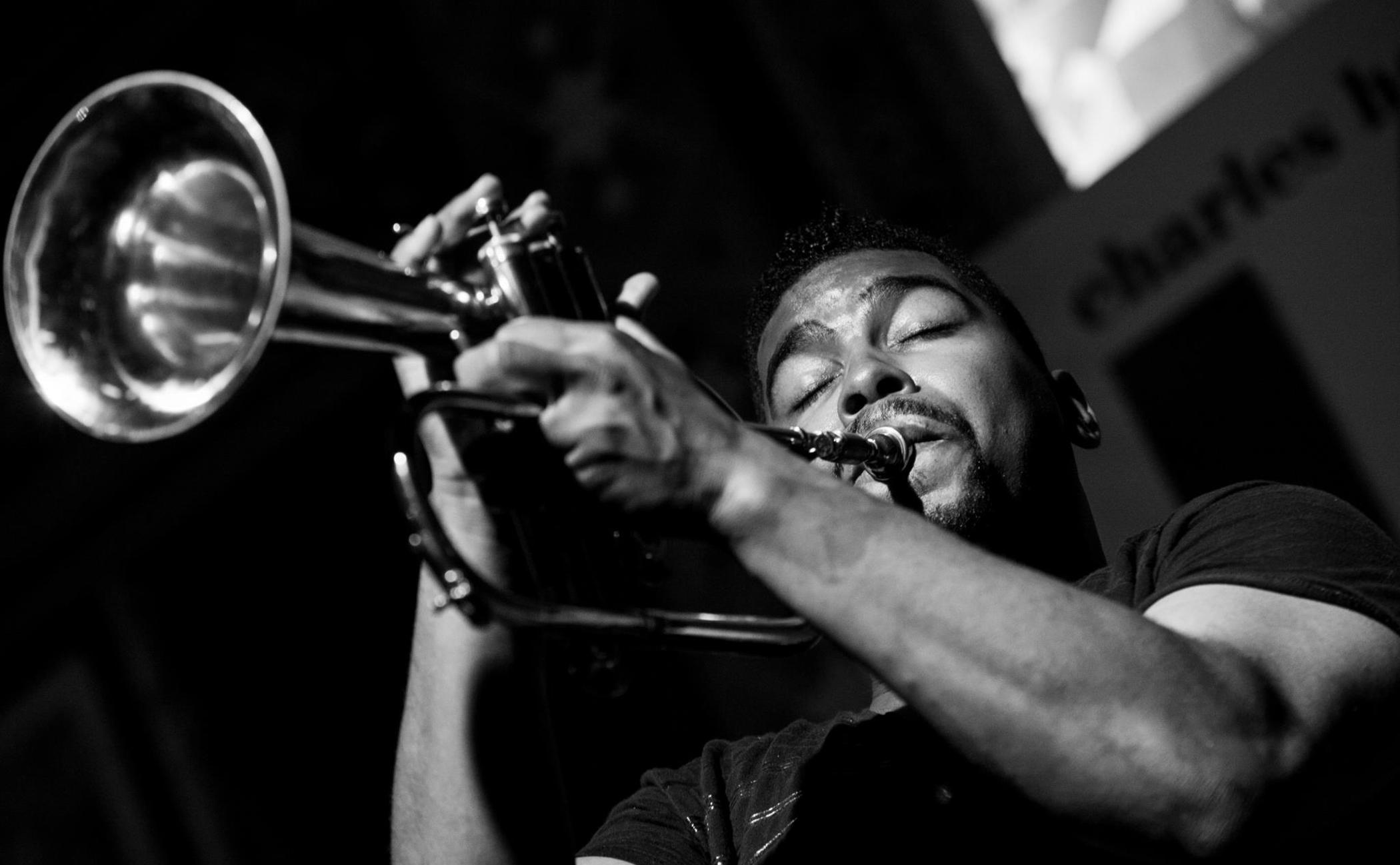 A dark-skinned person with mustache and goatee plays a trumpet with their eyes closed.