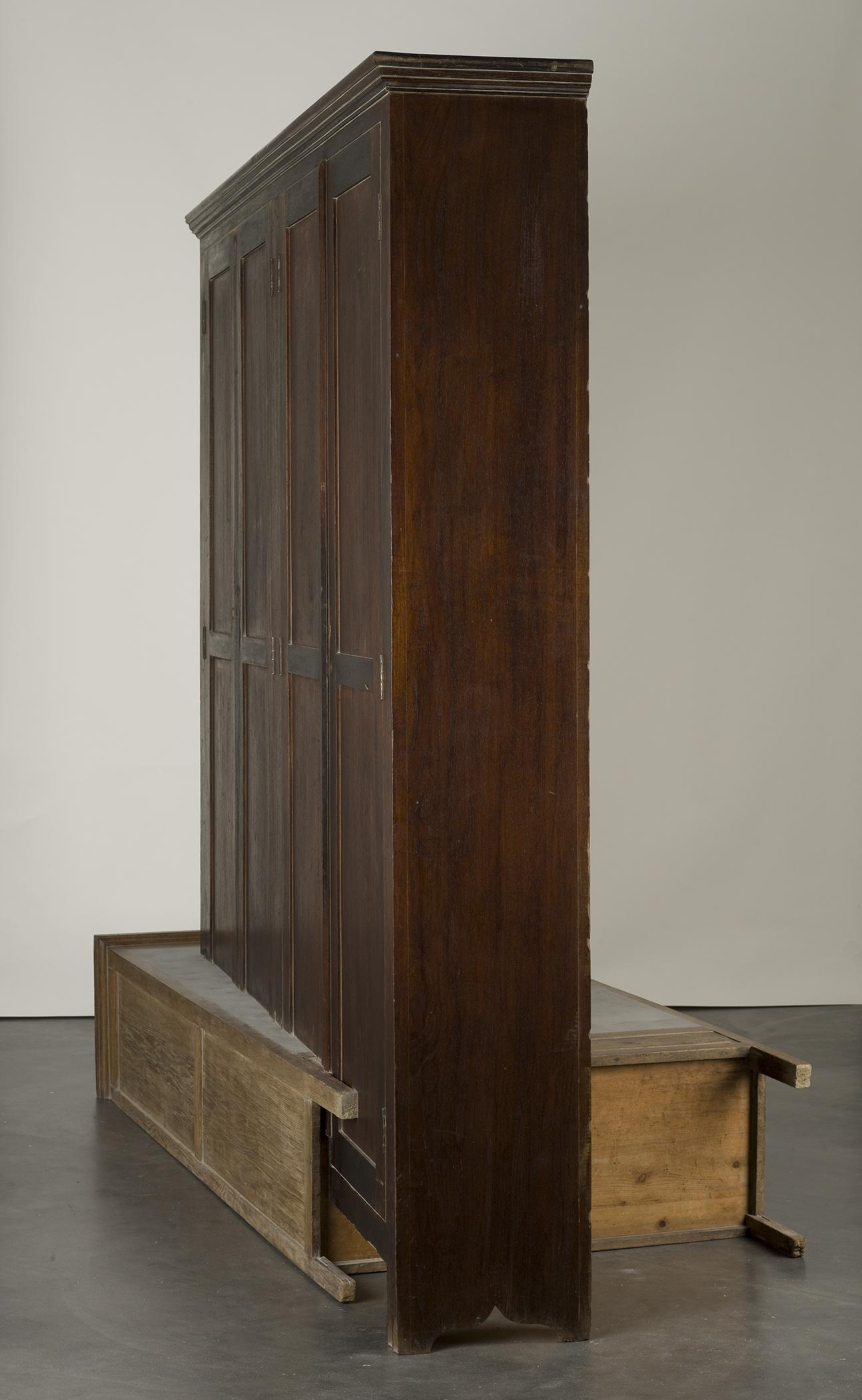 A vertical wooden cabinet precisely intersects a second wooden cabinet laying on the floor.