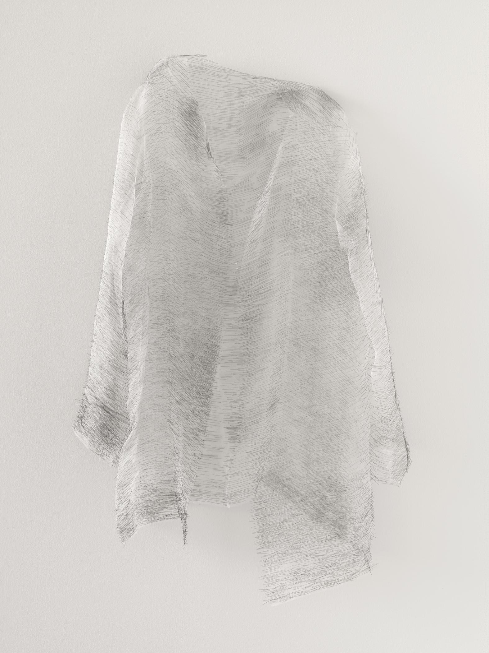 A piece of nearly translucent gray cloth hangs effortlessly off the wall in a shape reminiscent of a ghost.