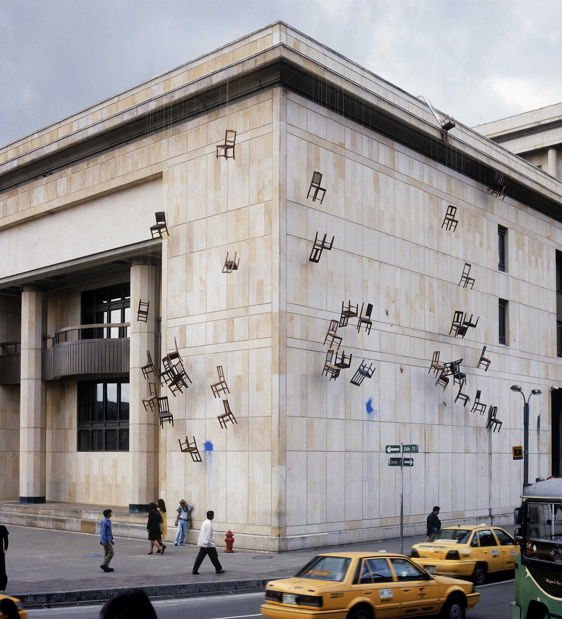 A building has several dozen chairs hanging off its roof and down the side, suspended by rope.