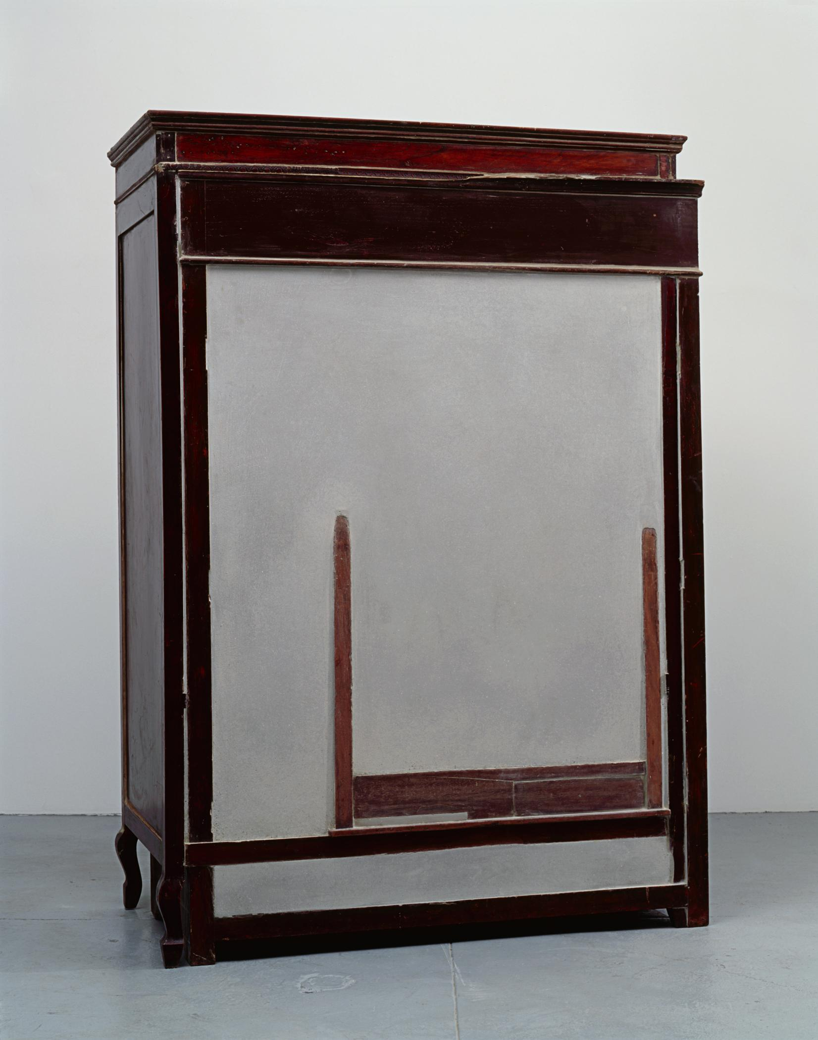 A wooden cabinet filed with cement has a barely visible second piece of furniture peeking out the surface.