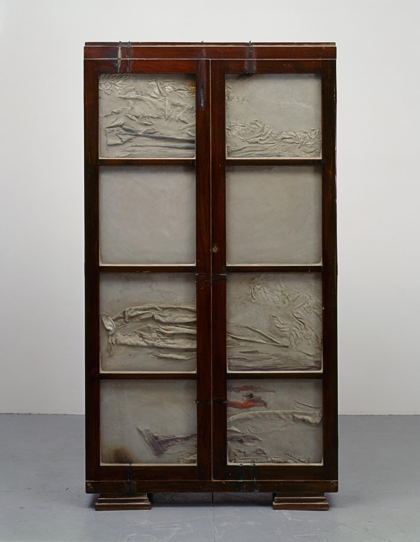 A sculpture of a wooden chest is filled with cement that has creases and ripples on the surface.