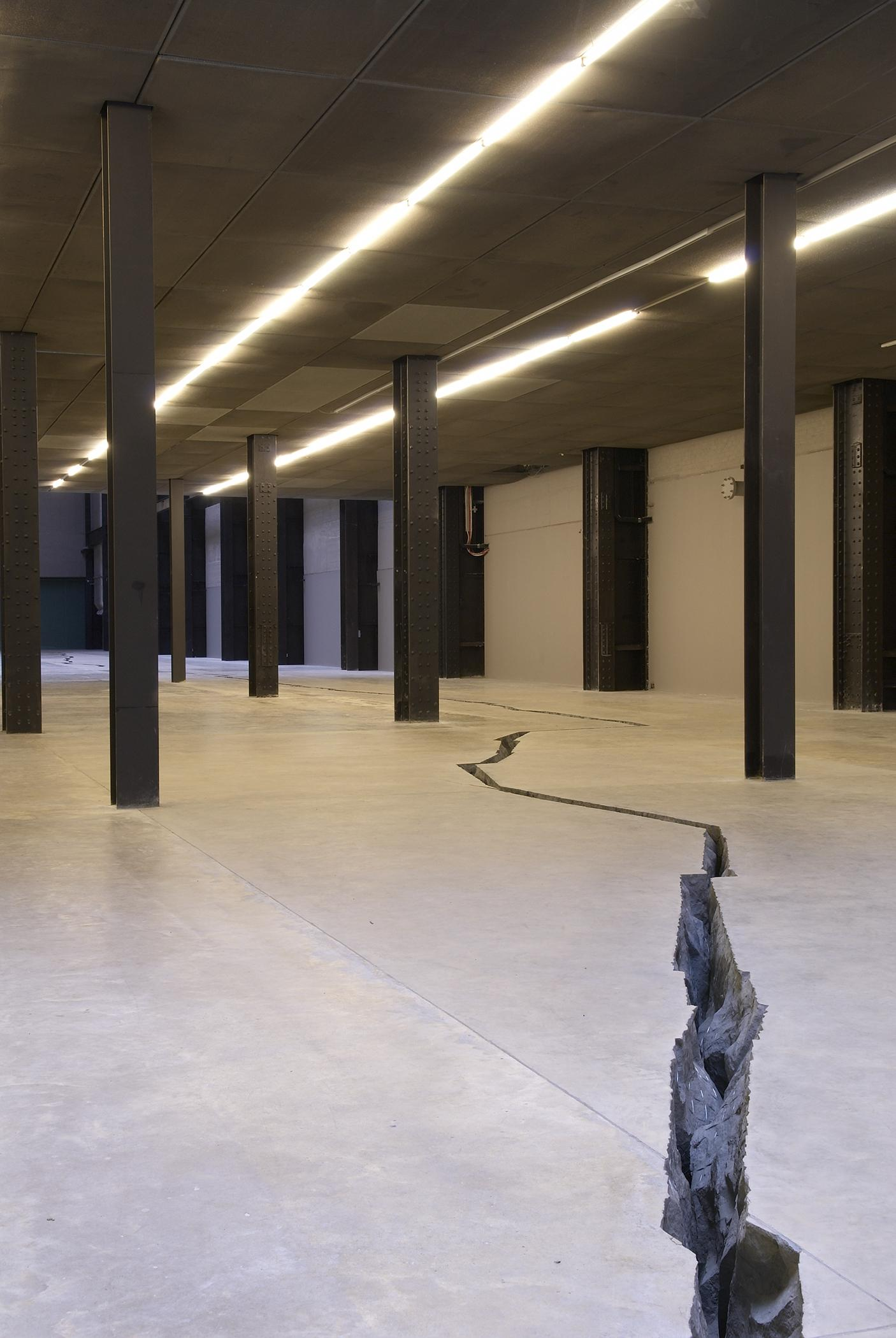 A photograph shows a room with several black columns and a crack in the floor running between them.