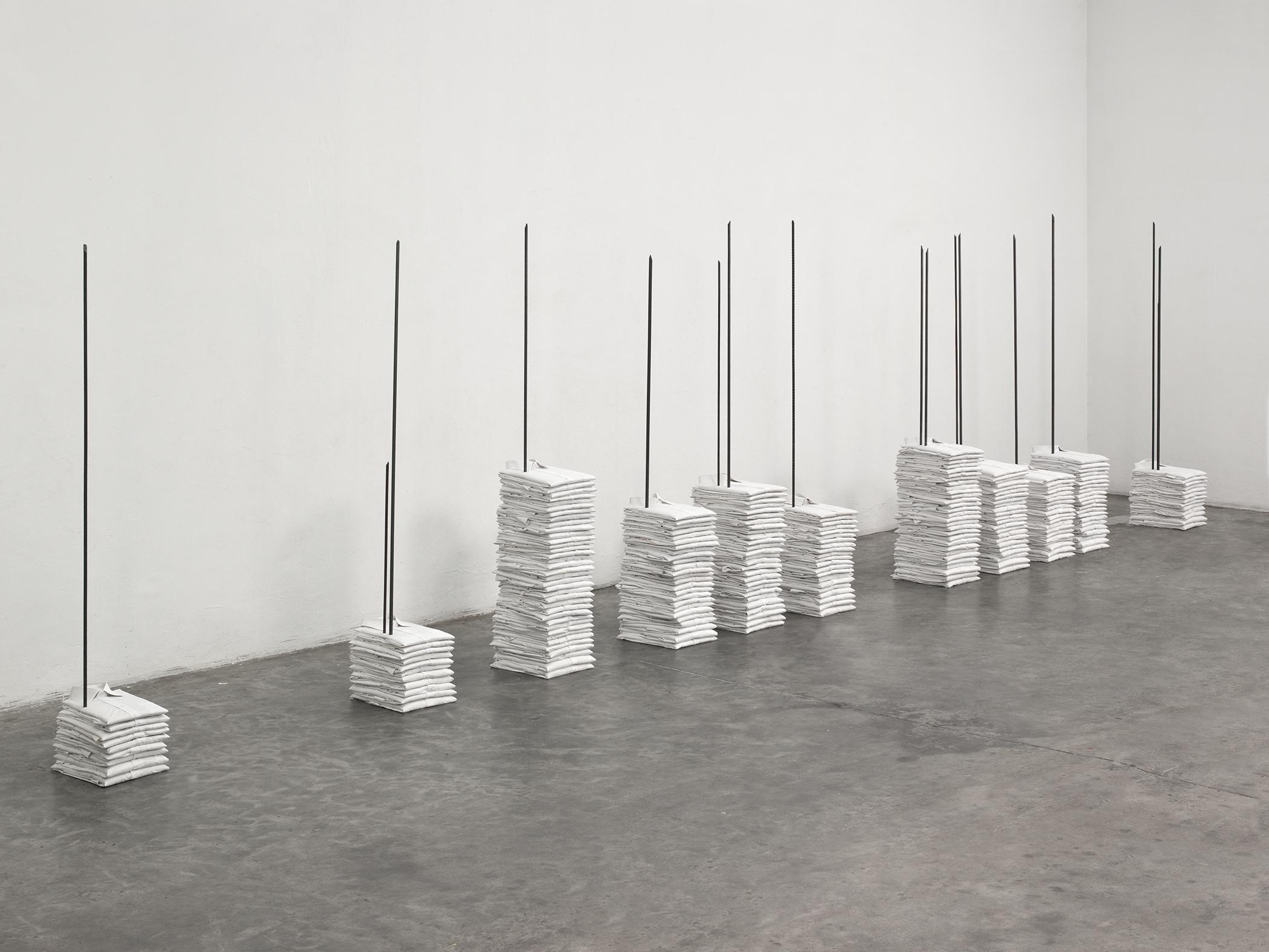 A sculpture shows several stacks of folded white polo shirts that are pierced by metal rods sticking out of the floor.