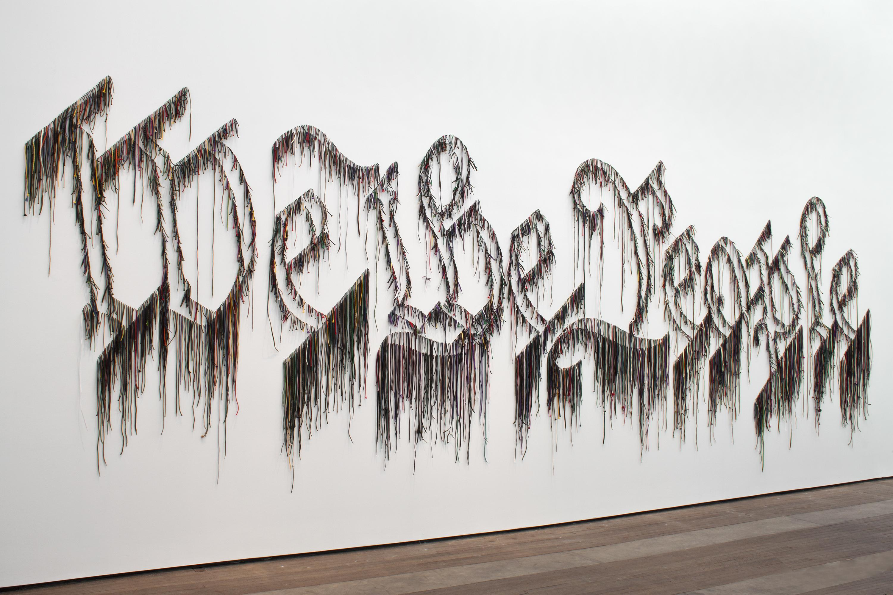"""Colorful strands hung on a white wall spell out the phrase """"We the People"""" in outlined letters that seem to drip."""