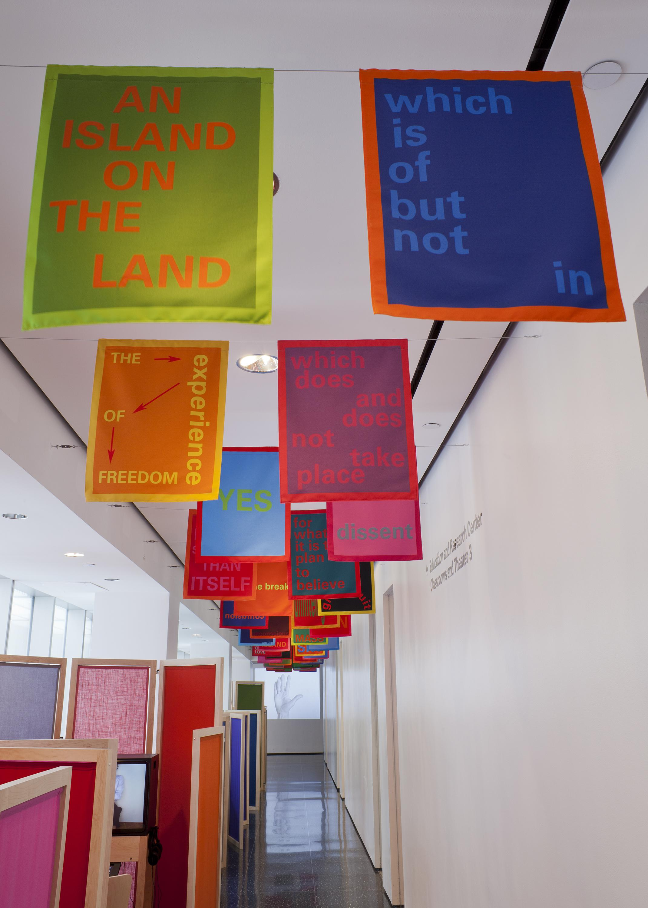 Multicolored banners with text are hung in pairs from the ceiling. Below, wooden and fabric room separators run the length of a white gallery.