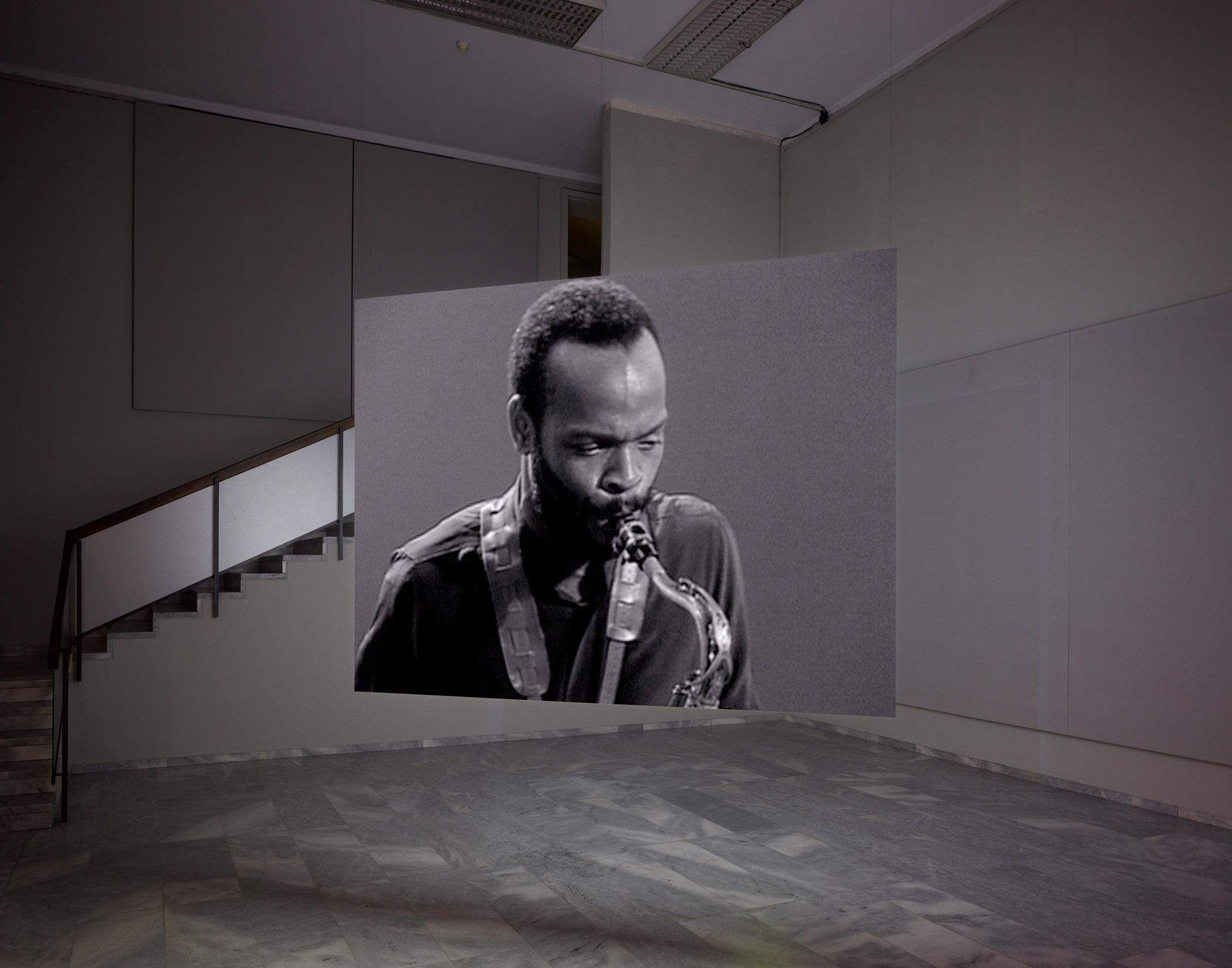 A portrait of a man playing saxophone is seen on a screen suspended from wires in the middle of a room.