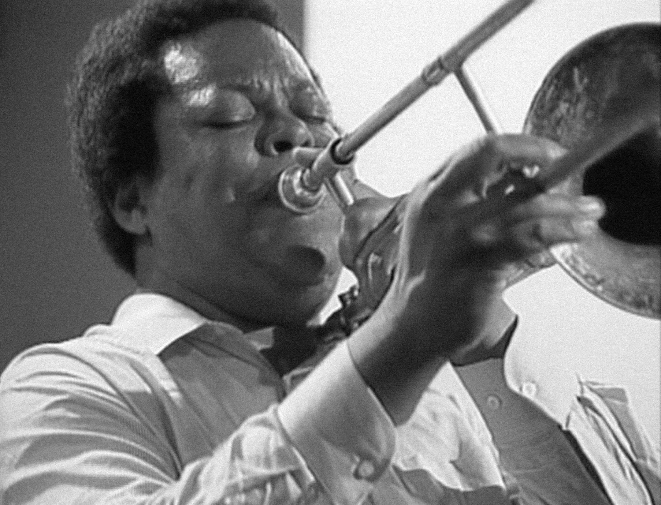A black-and-white portrait shows a dark-skinned man with a short afro playing the trombone.