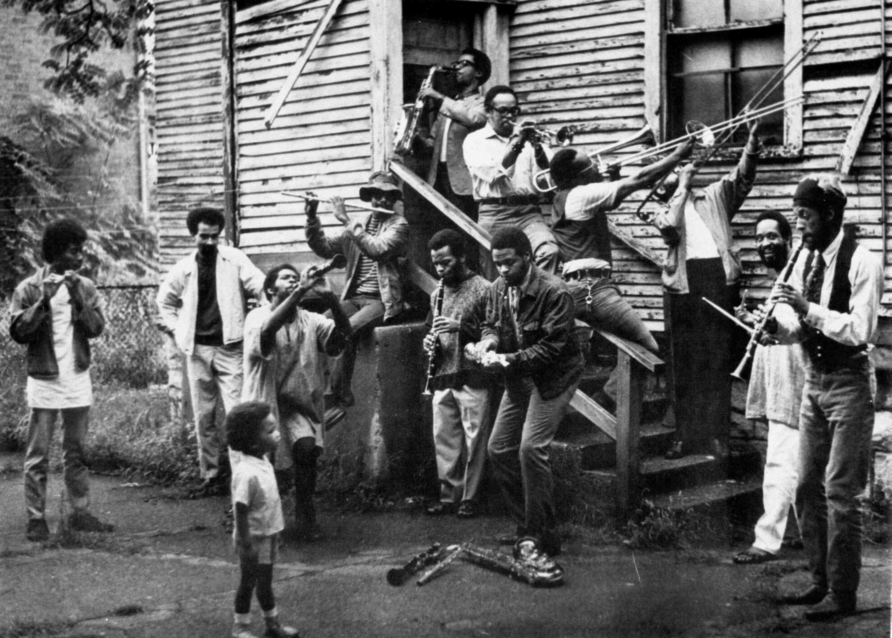 A black and white photograph of a crowd of men joyously playing all kinds of musical instruments on a porch while a young boy looks on