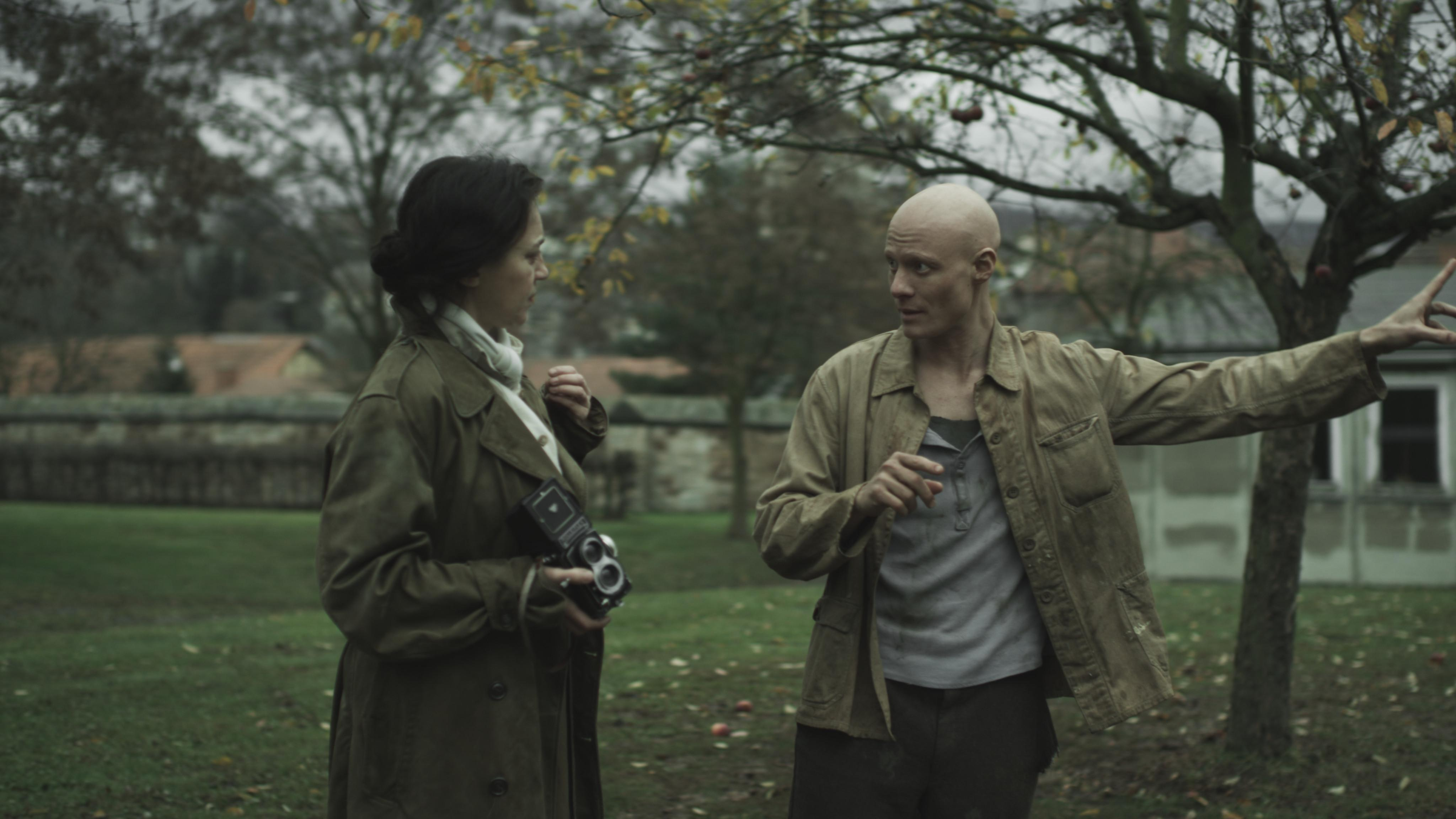 In an outdoor setting, a young bald person reaches their left arm out while looking at a feminine person wearing a trench coat and holding a camera.
