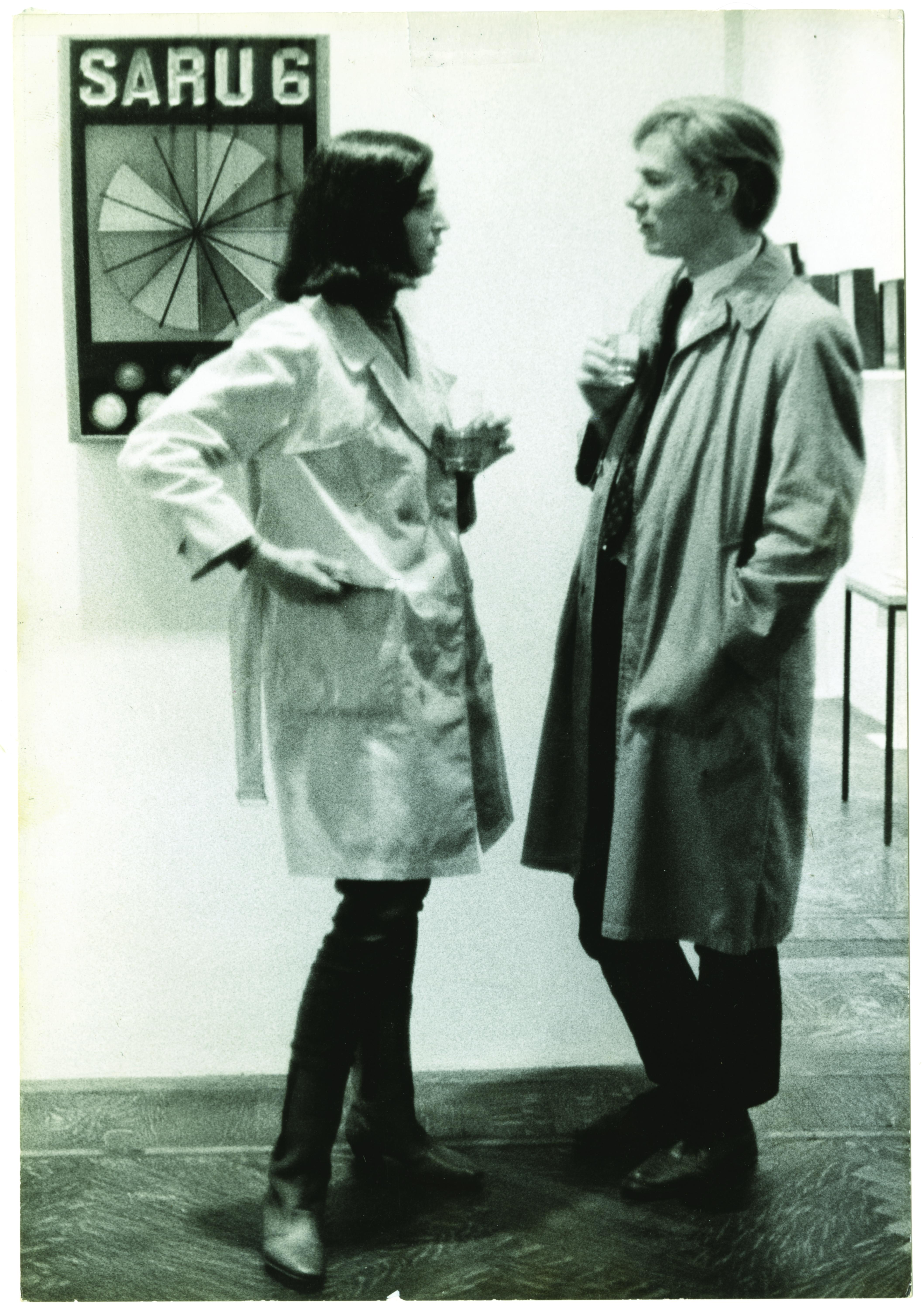 A dark-haired woman and blonde-haired man wearing trench coats and holding drinks stand facing each other in front of an artwork.