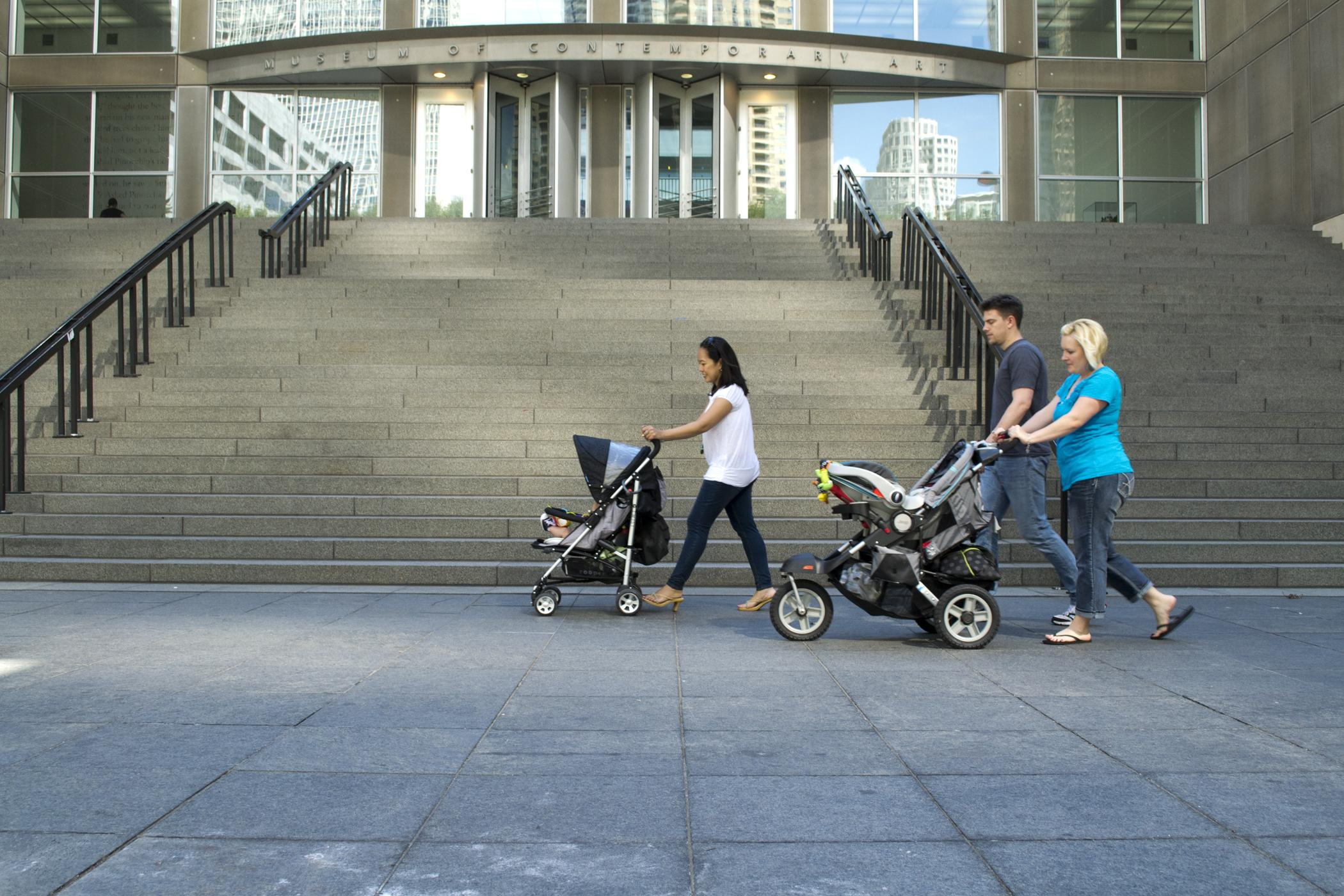 Three young people walk across the MCA plaza on a warm day, two push strollers.