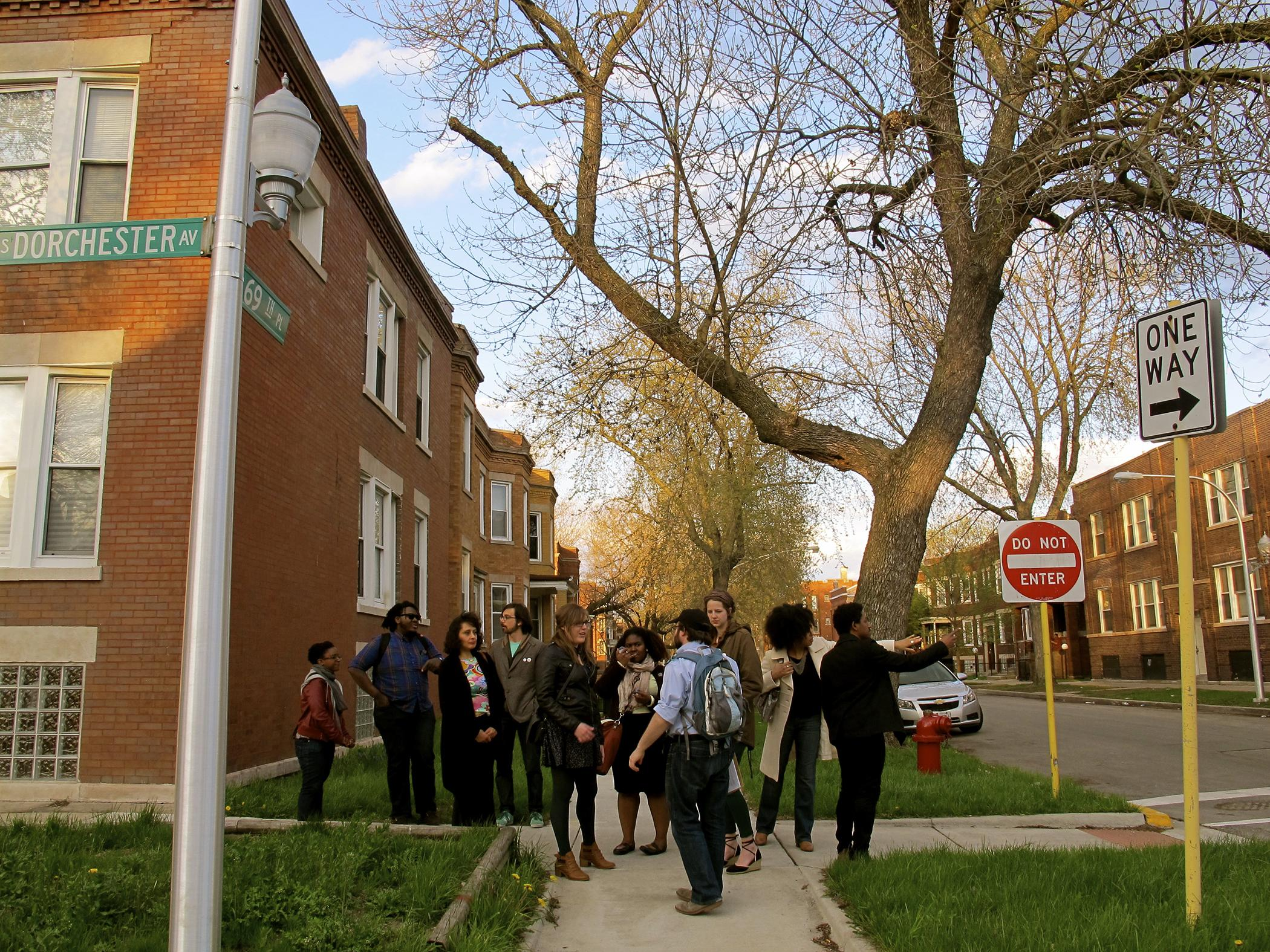 """A group of young people of different races are clustered at the end of a sidewalk as a man wearing a backpack leads them; the street signs in the image say """"Dorchester Avenue"""" and """"69th Place."""""""