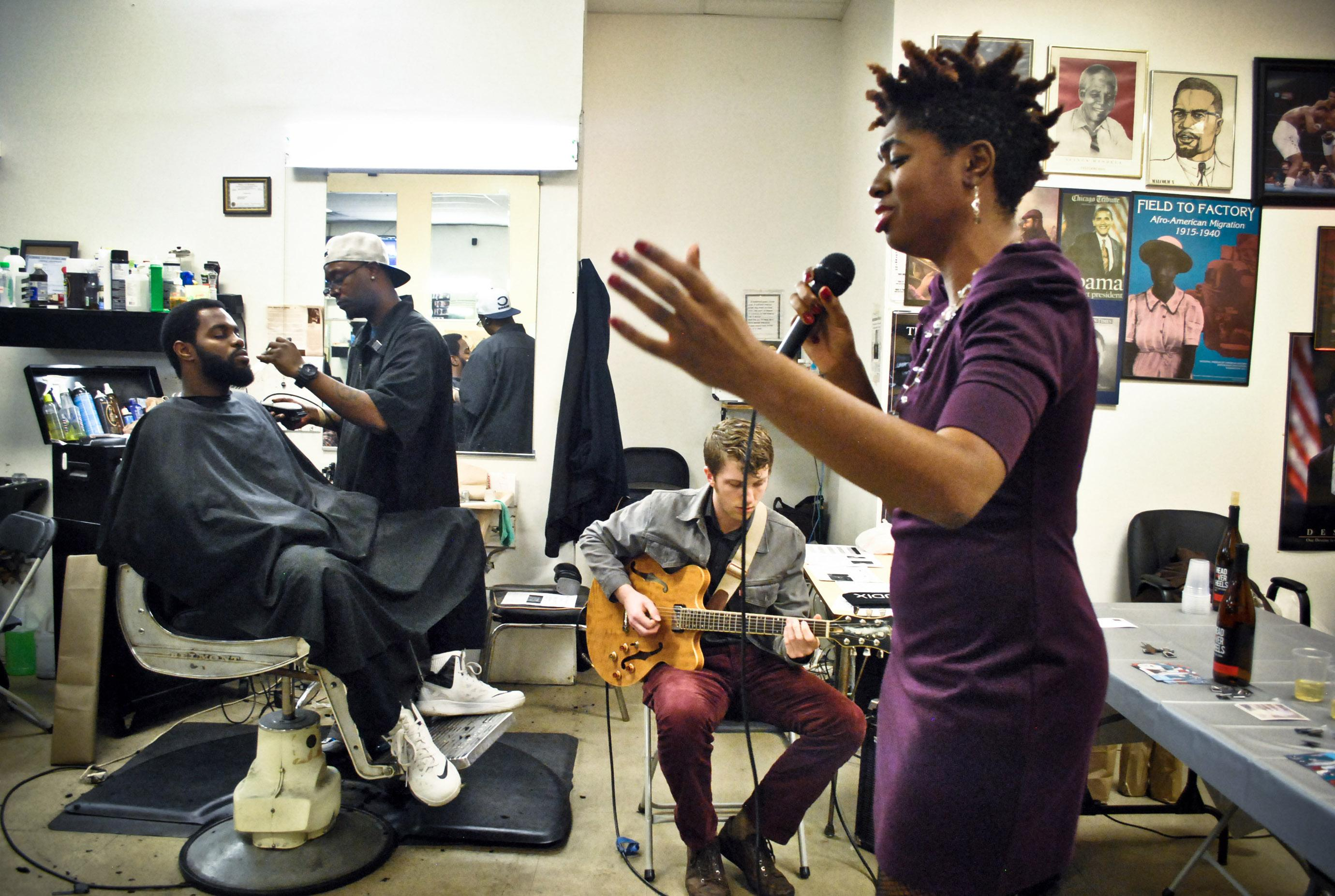 A young black woman sings into a microphone in a barbershop; a young white man sits behind her playing electric guitar. To his left a black man sits in a barber's chair getting his hair cut.