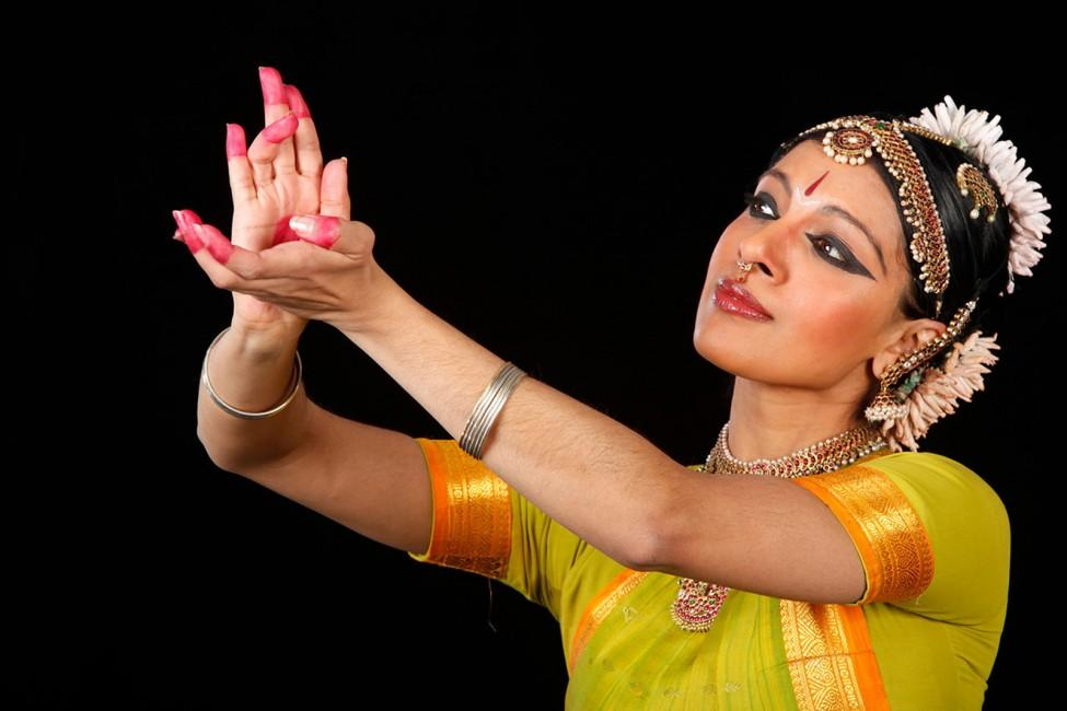 A woman wearing an Indian sari and elaborate headwear and jewelry, her eyes outlined in heavy black kohl, reaches out her arms and gestures with red-tipped fingers while looking in the distance.