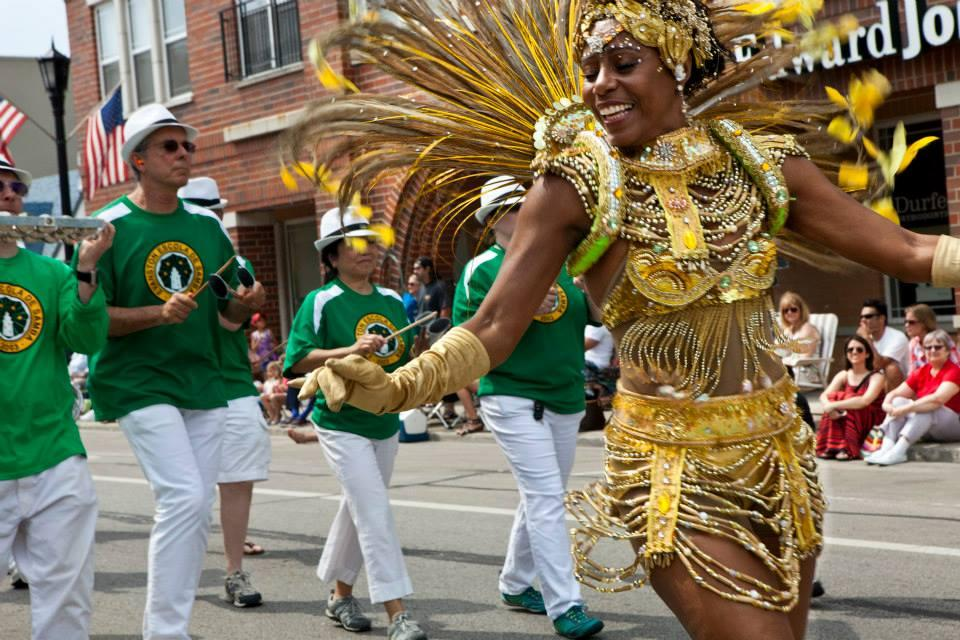 A Samba showgirl dressed in an elaborate gold feather and beaded costume leads a parade with a marching band following behind her on a hot summer day.