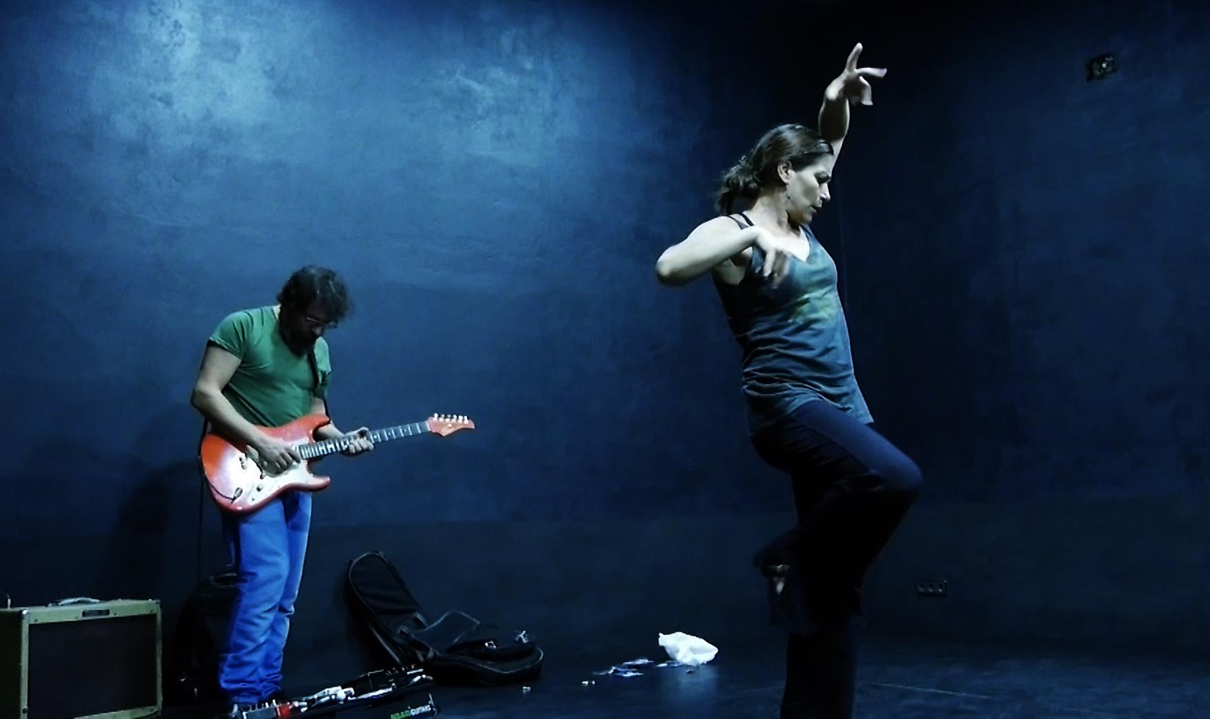 A woman wearing everyday clothes dances in a contemporary Flamenco style on a dark blue stage; behind her a man plays an electric guitar .