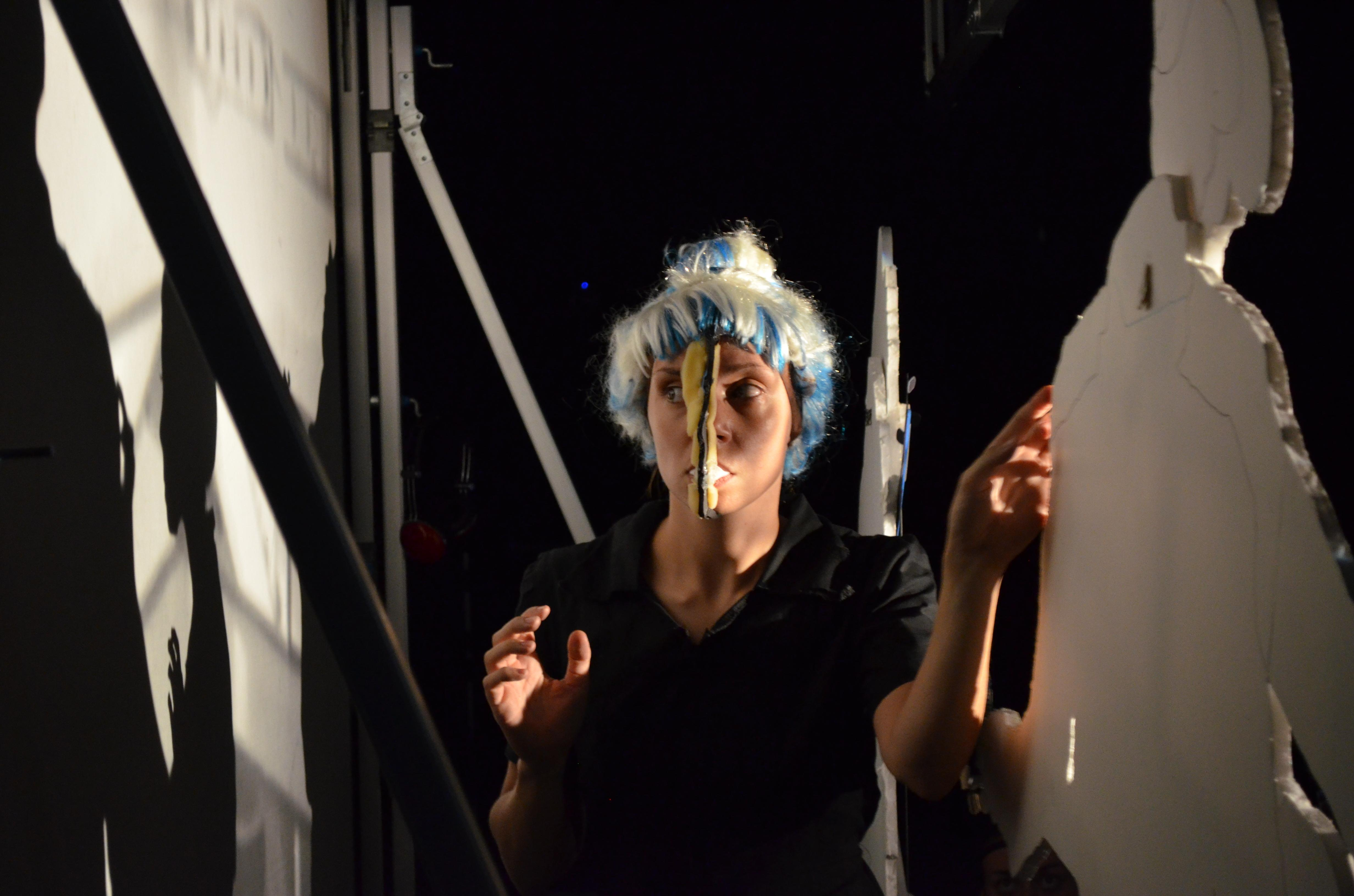 A woman wearing a white and blue wig holds part of a mask with her teeth and touches a cardboard cut-out with her left hand, casting a shadow on a screen to her right.