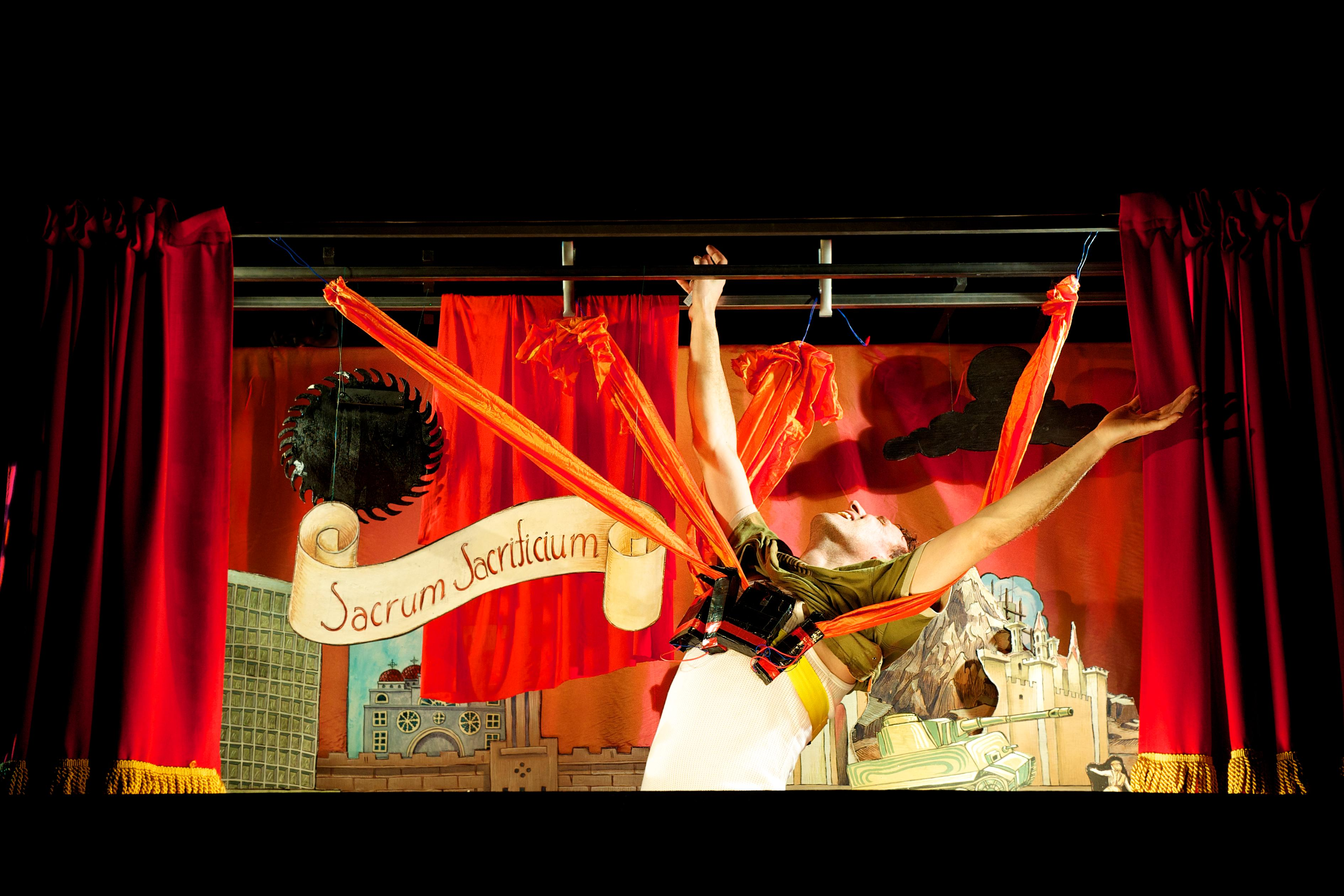 """A man caught in red fabric flares his hands upward in front of a miniature stage set that is made of red curtains, painted paper, and a paper banner that reads: """"Sacrum Sacridicium."""""""