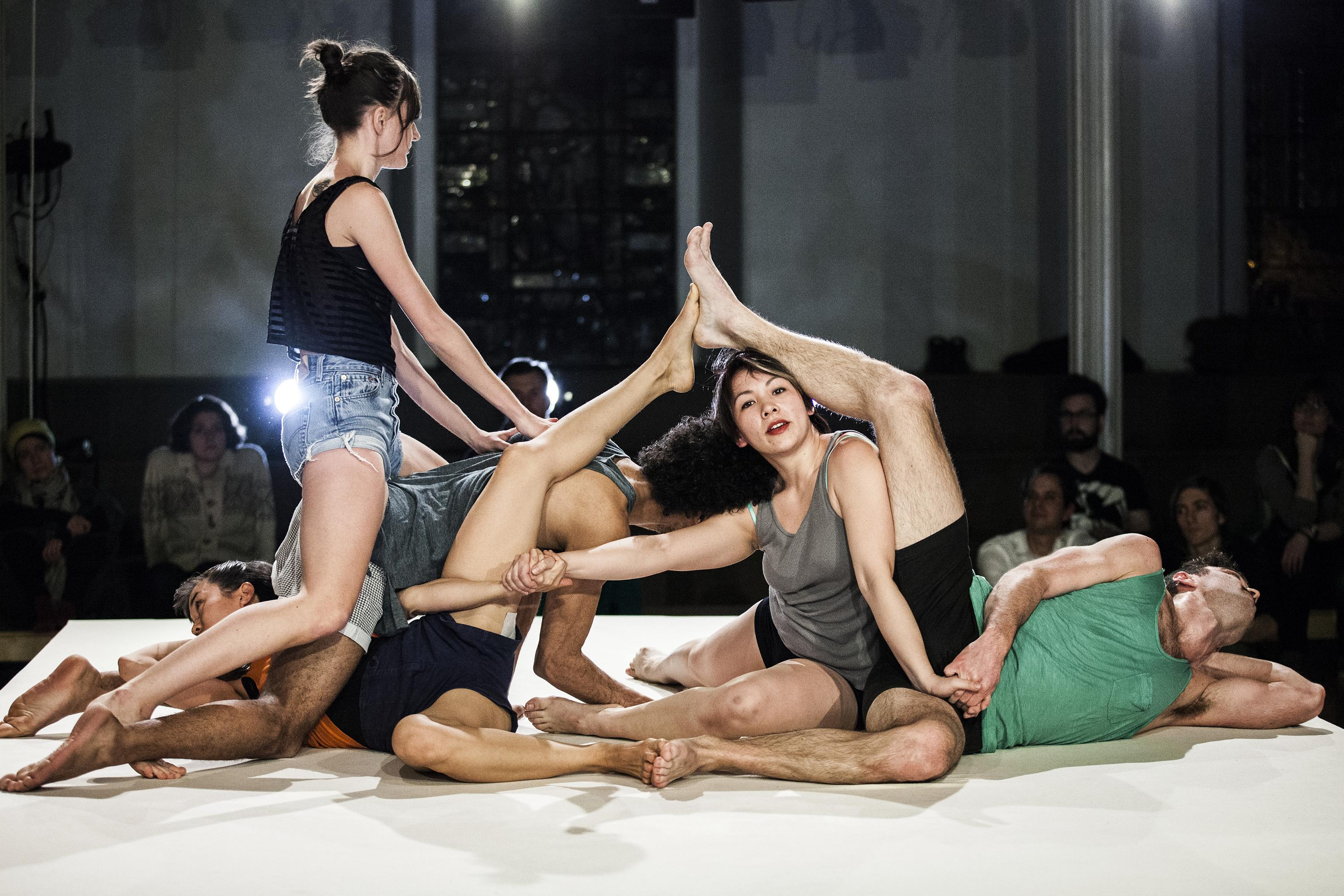 Five coed dancers lie entwined on a small stage