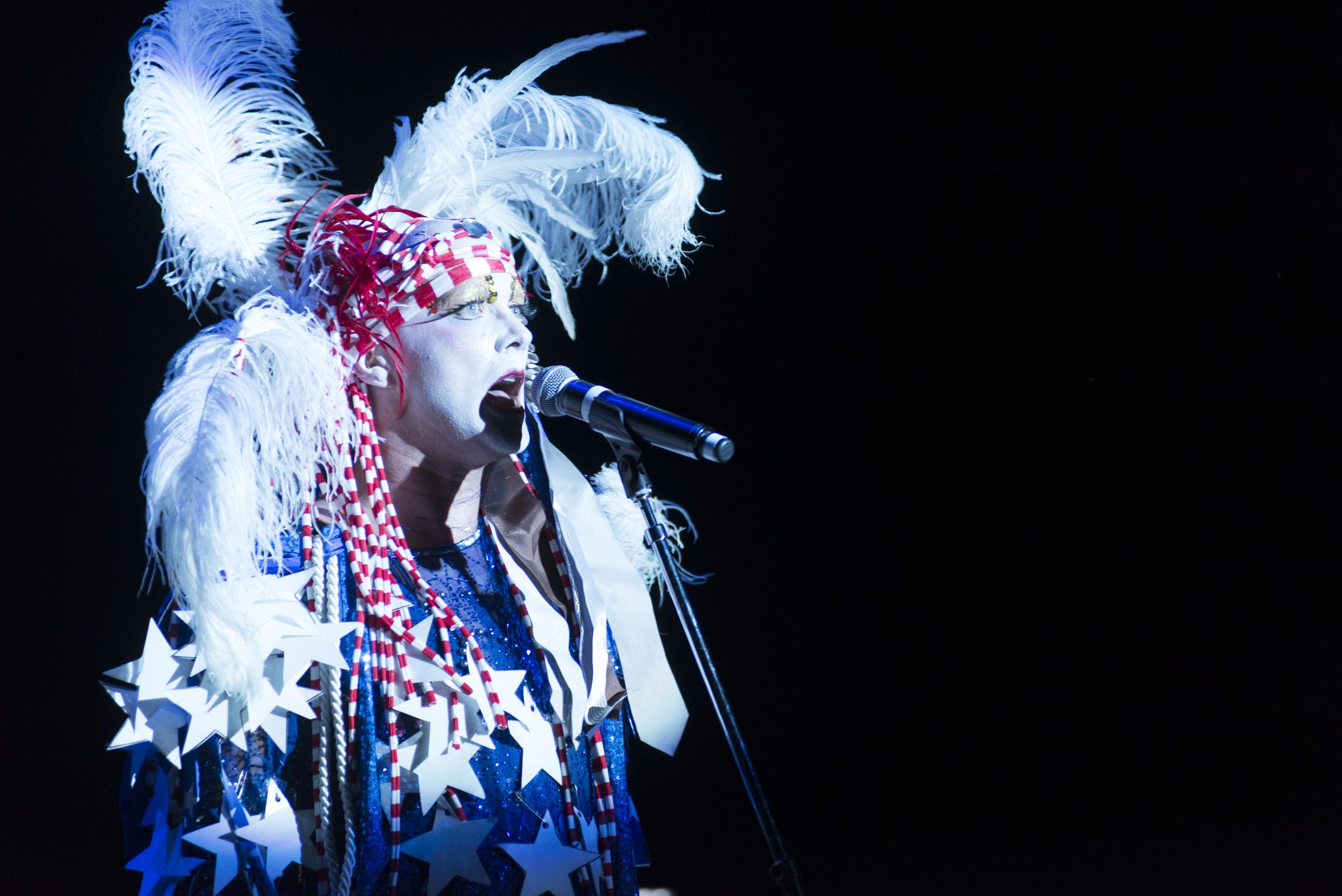 A person sings at a microphone on a pitch-black stage, wearing a white feather headdress, a red-striped bandana, and blue dress strung with white paper stars.