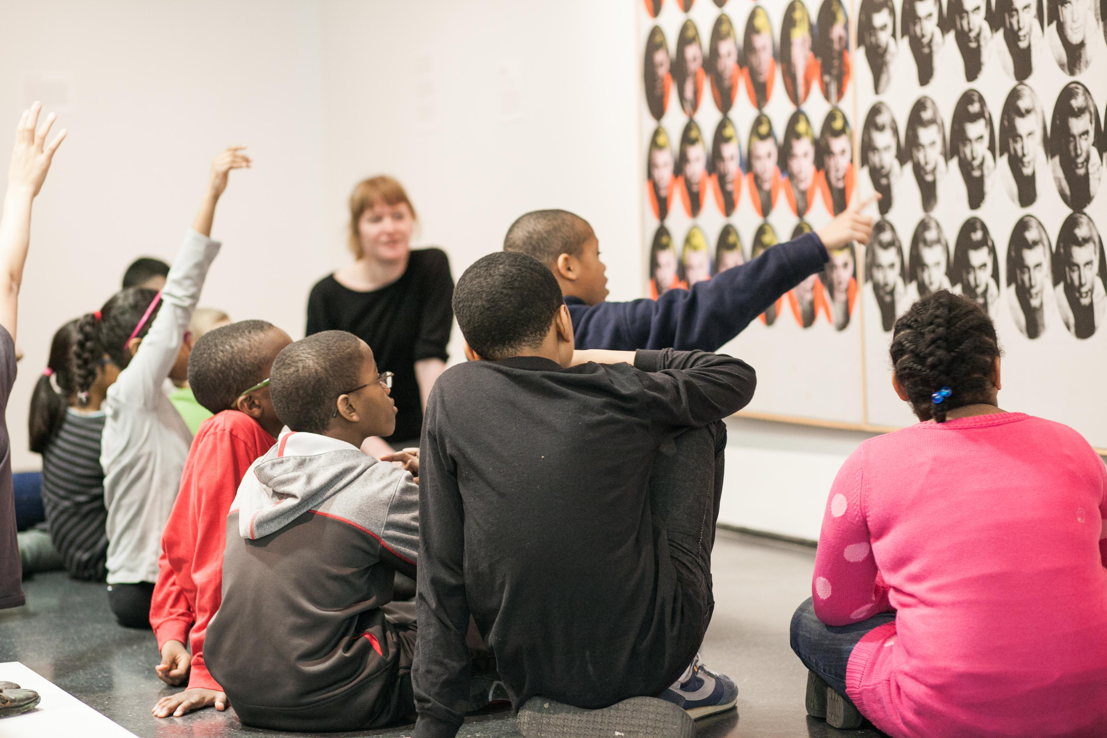 A group of kids and an artist guide look at an artwork in a gallery. Several raise their hands as if ready to answer a question.
