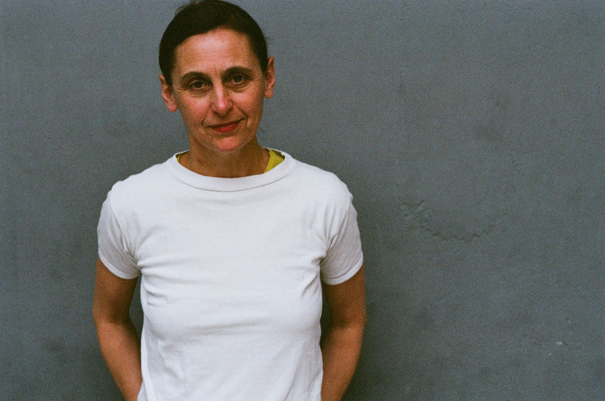 A person with short, dark hair wears a white tee shirt and regards the viewer calmly while standing before a medium-gray wall.