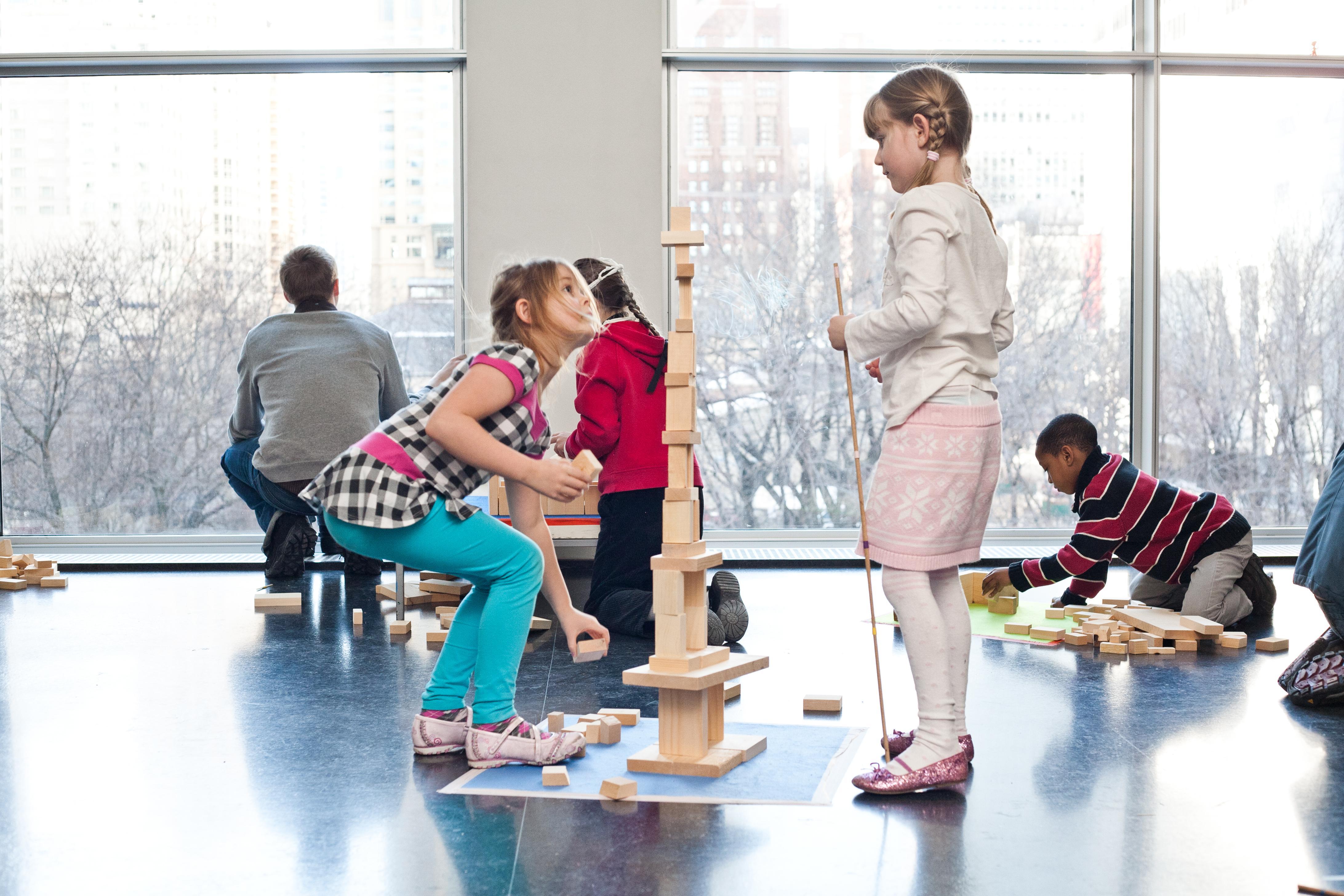 In an open indoor space, children play with wooden building blocks on the floor.