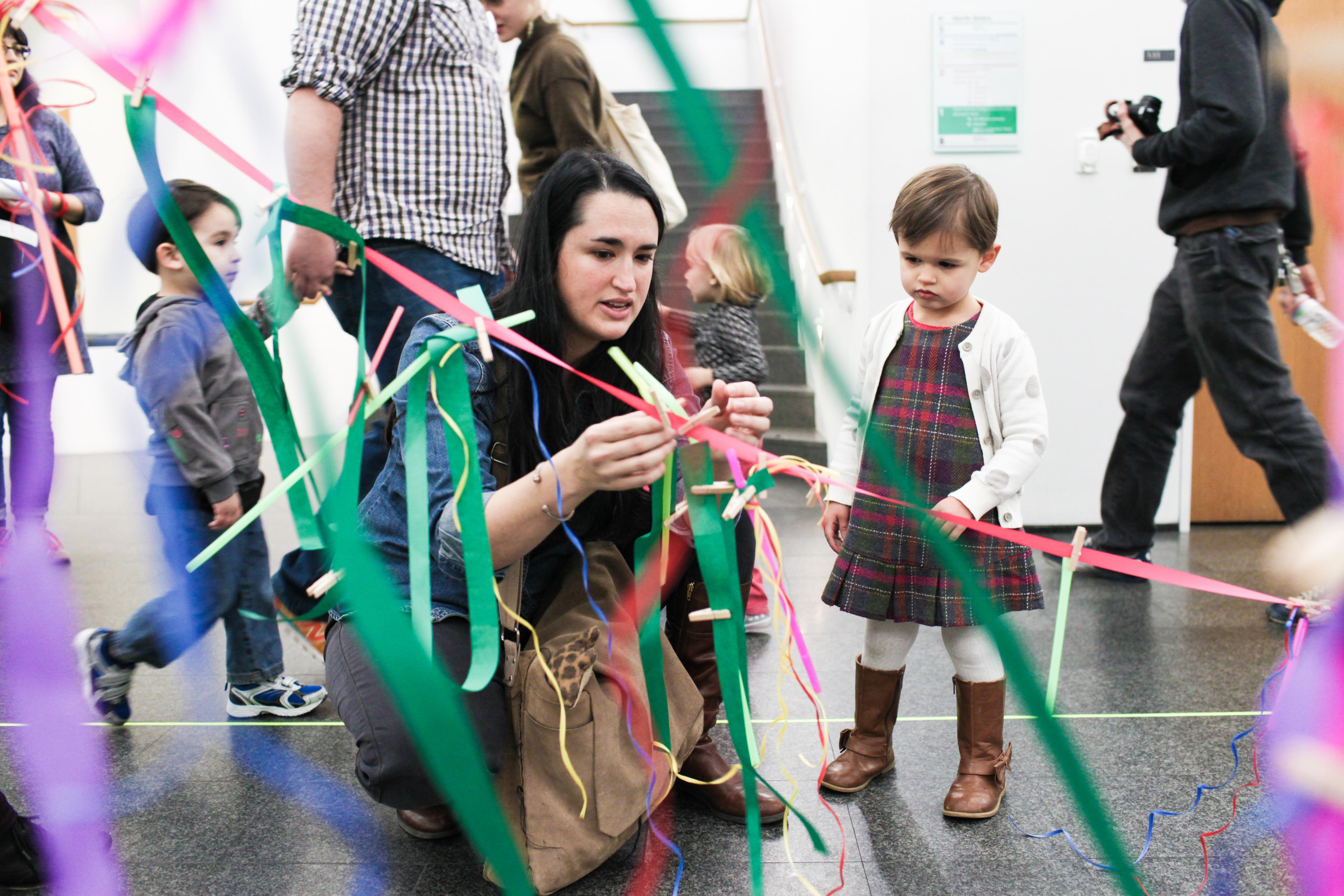 A woman ties a knot of ribbon onto another while a young child watches.