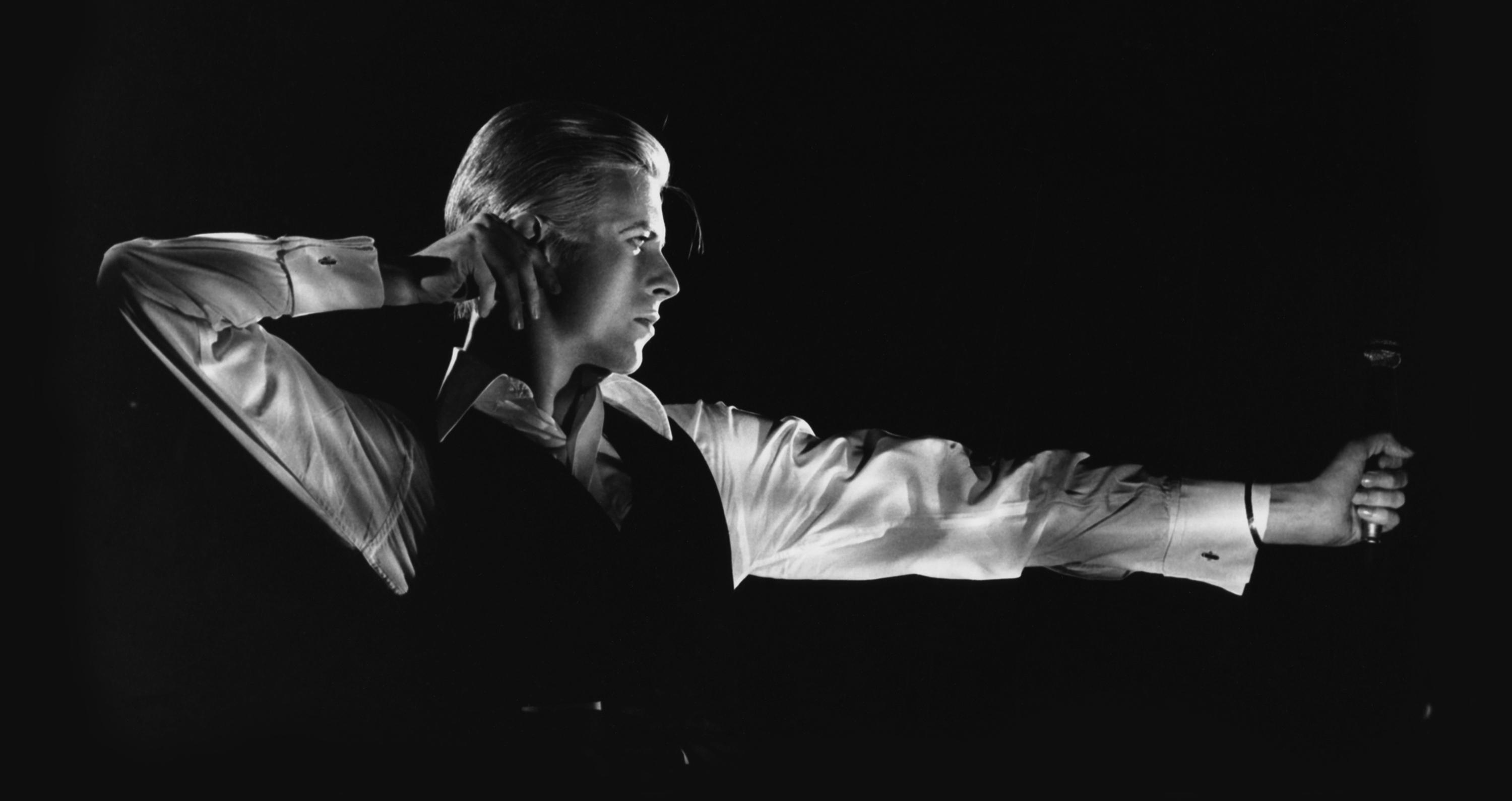 Black-and-white portrait of David Bowie in profile, arms positioned as though shooting a bow and arrow, a microphone in his extended arm