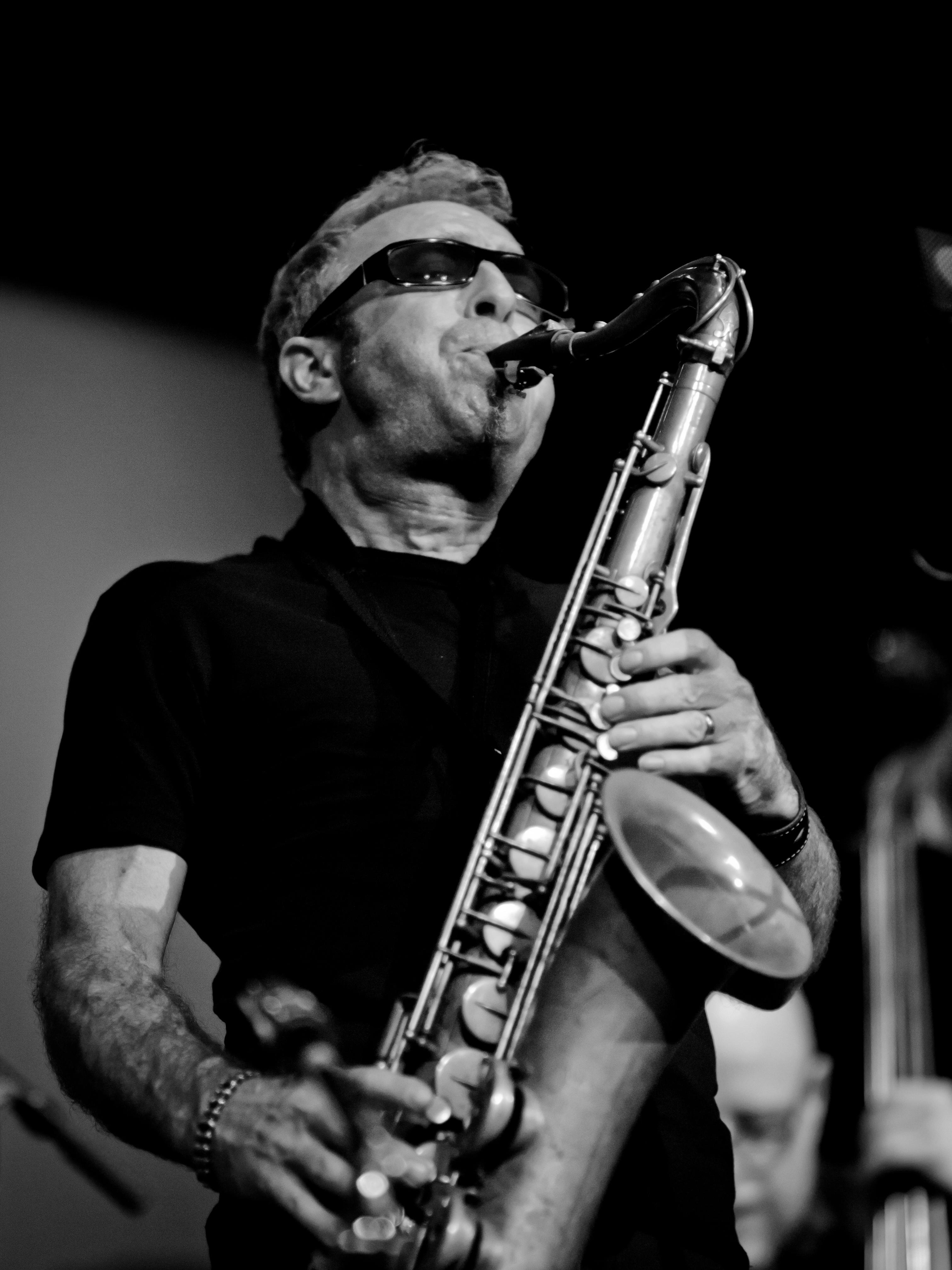 Black-and-white photograph of a man wearing sunglasses indoors playing a saxaphone
