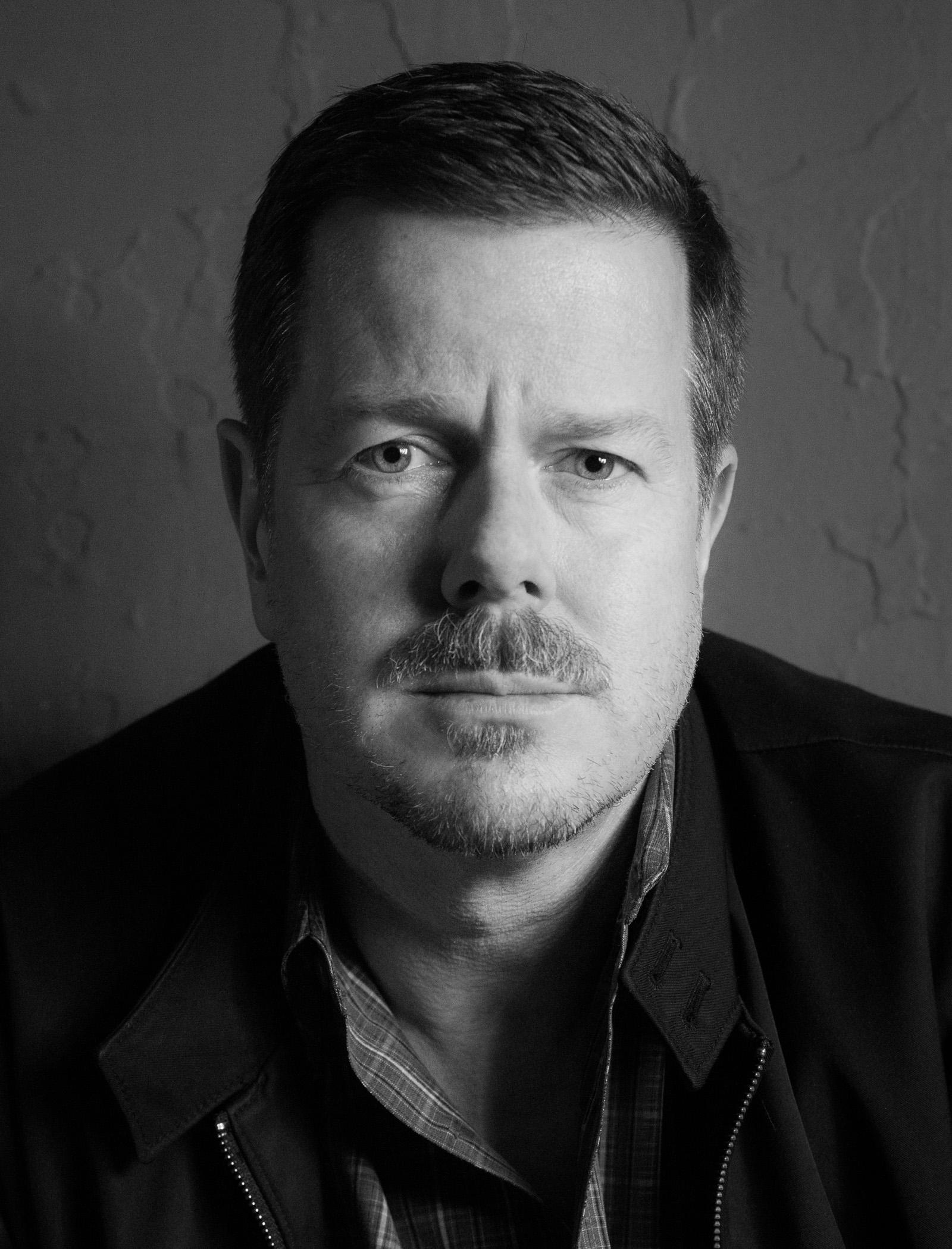 Black-and-white portrait of a man with a goatee looking directly at the camera