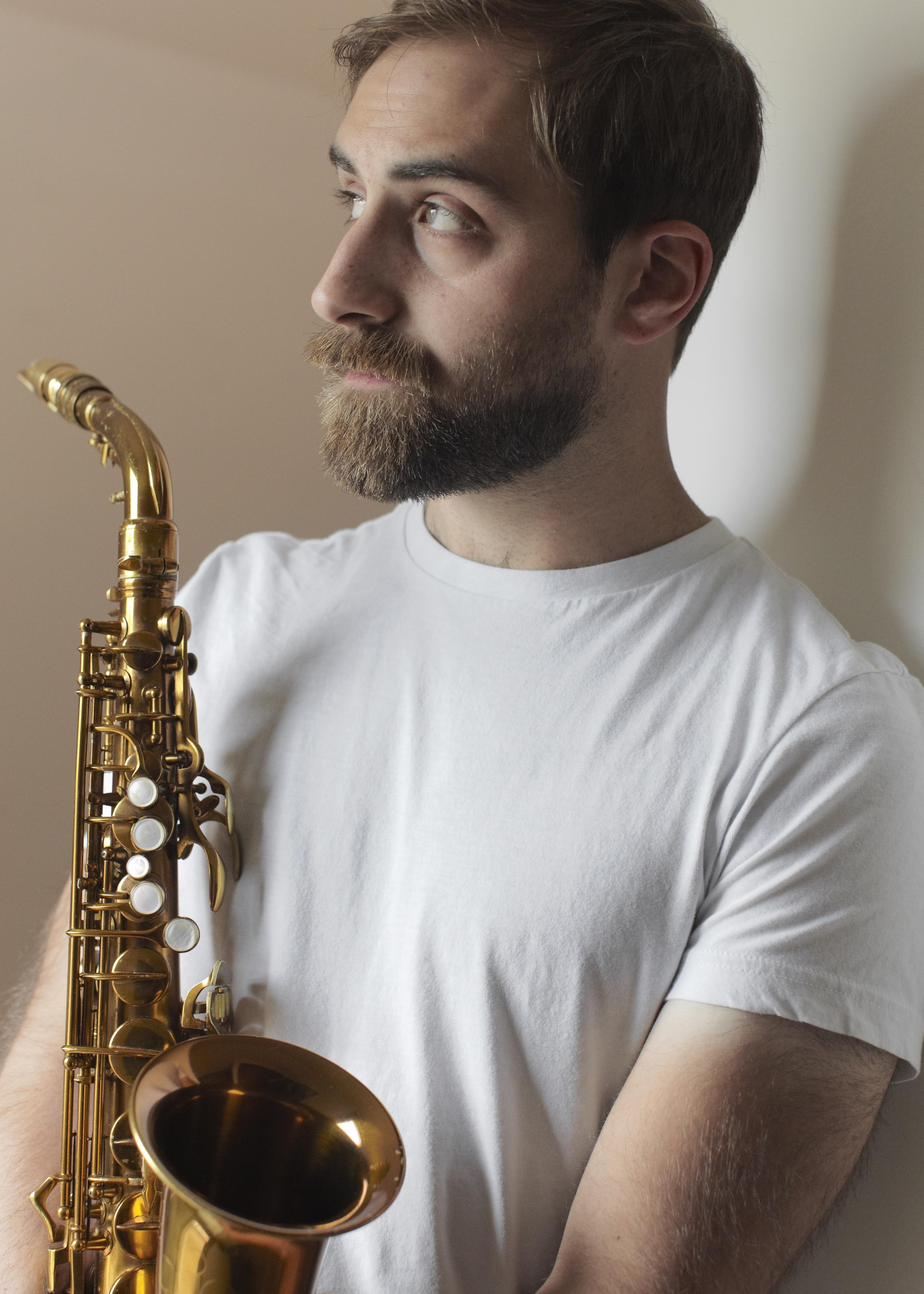 Portrait of a bearded young man holding a saxophone to his chest
