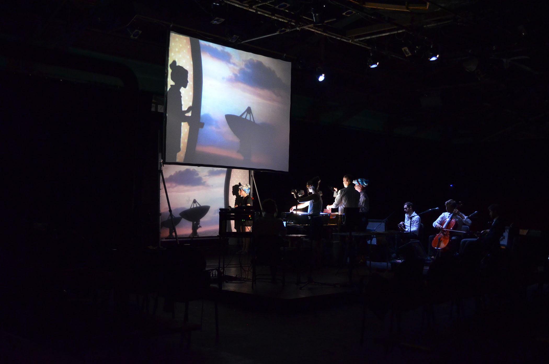 On a dark stage, technicians use overhead projectors to cast ta woman's silhouette onto an image of a sunset that appears in the background.