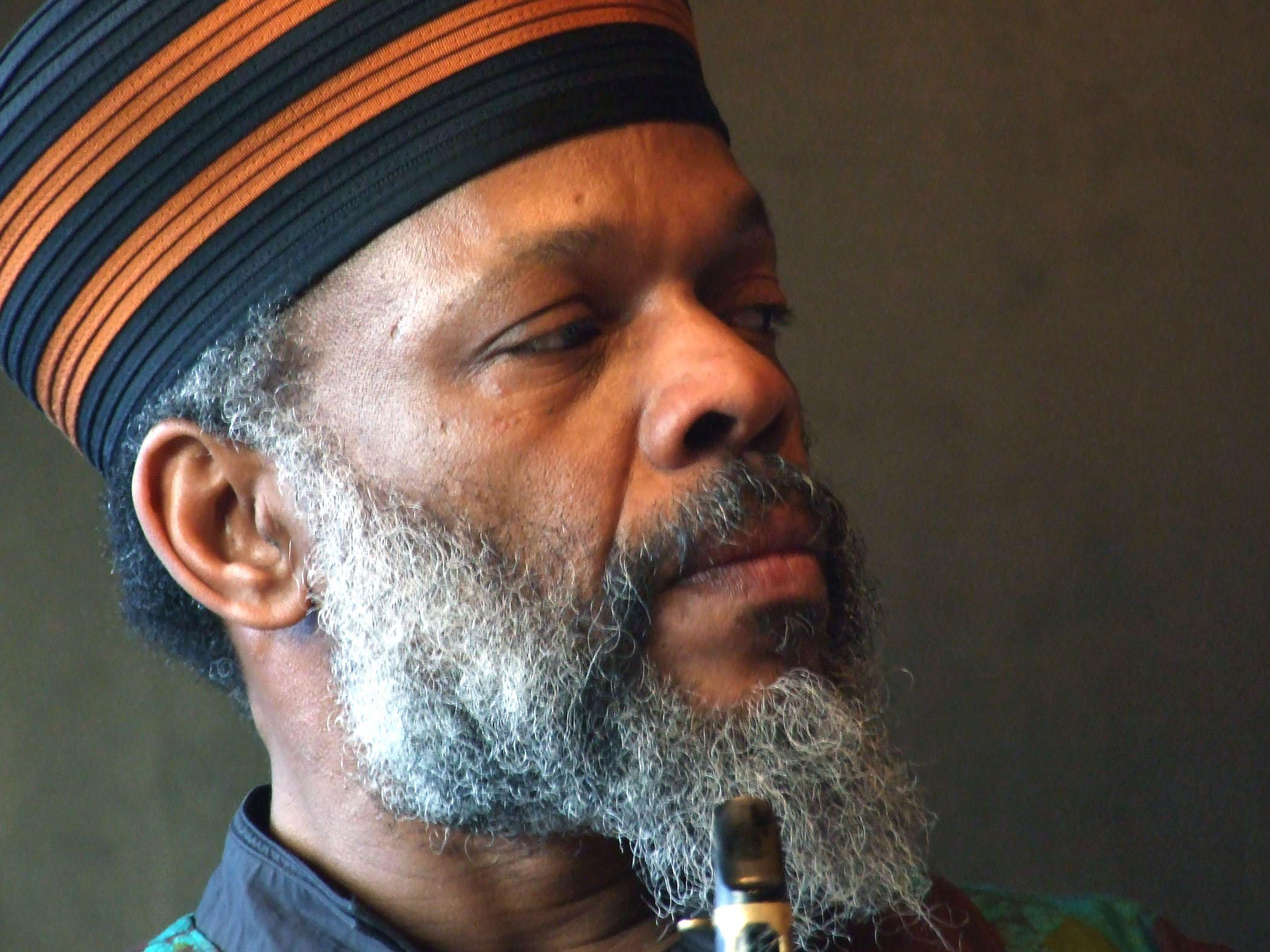 Portrait of a man with a long grey beard wearing a black and orange striped hat, the tip of a woodwind reed near his chin