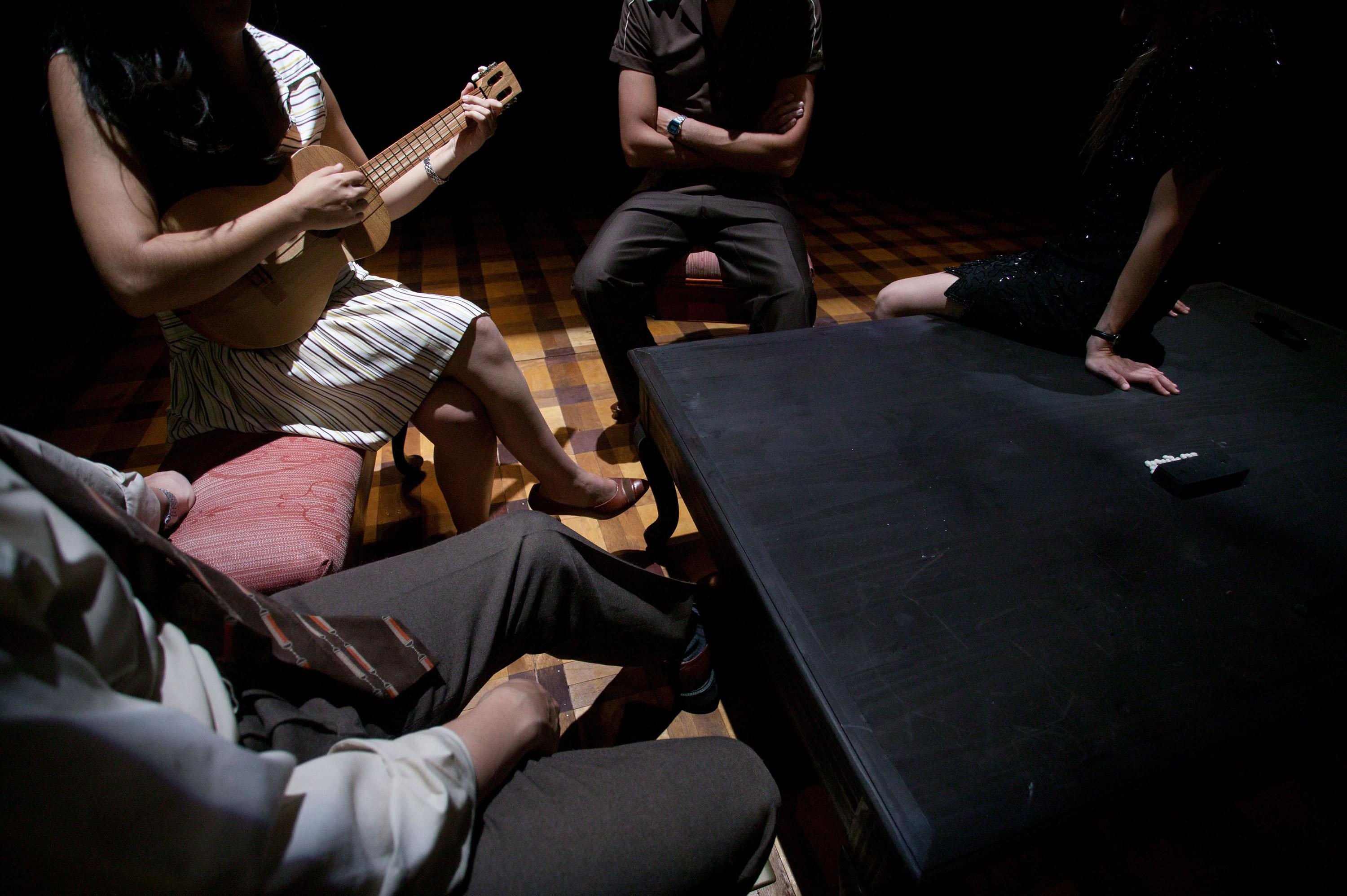 A closely cropped image of four people sitting around a table, one of them is playing a small guitar, we can't see their faces