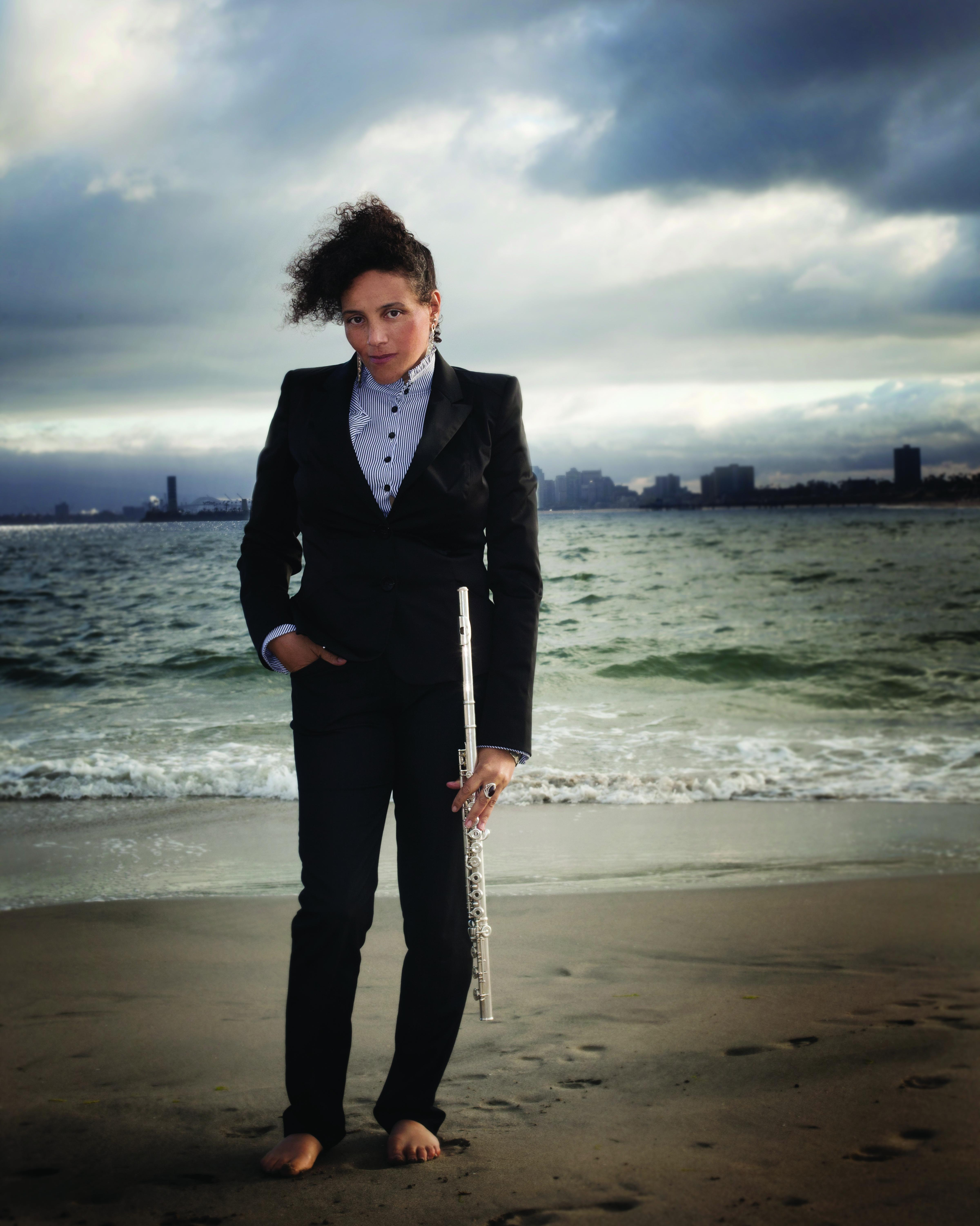A person in a black suit stands barefoot on a beach while holding a flute.