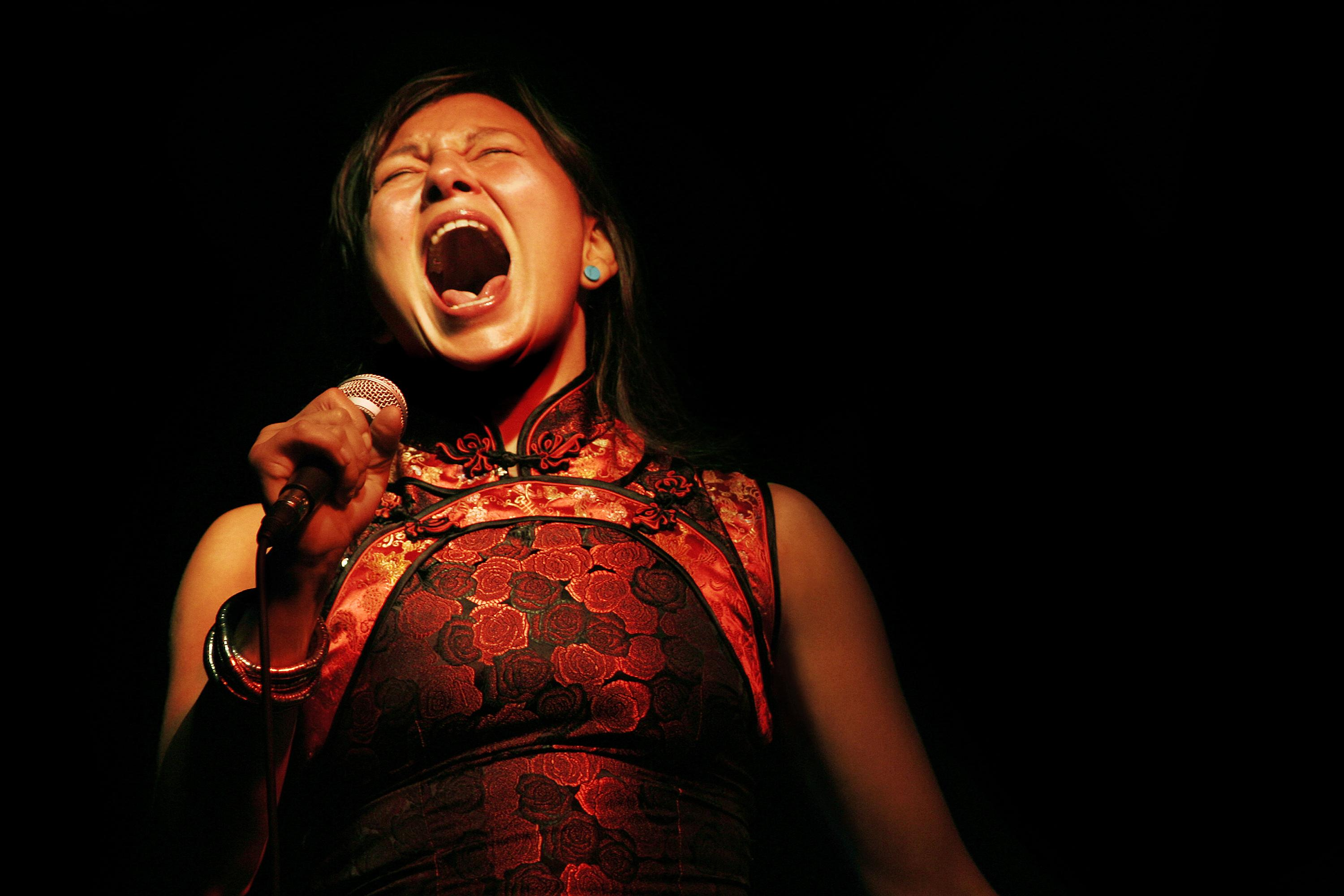 A woman in in Asian clothing sings into her microphone on a pitch-black stage
