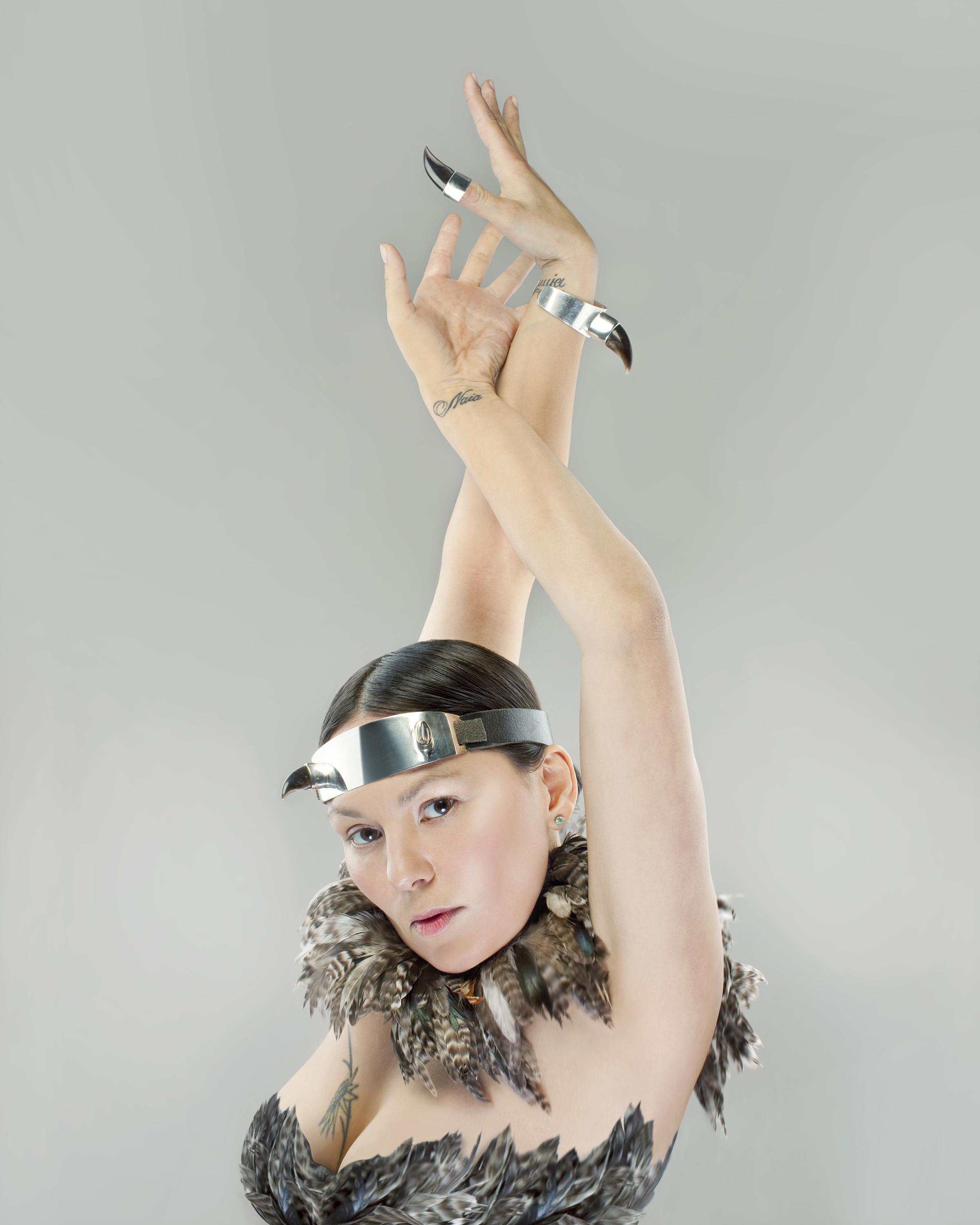 A woman posing, hands above head like a dancer, in feather garments and claw-like accessories