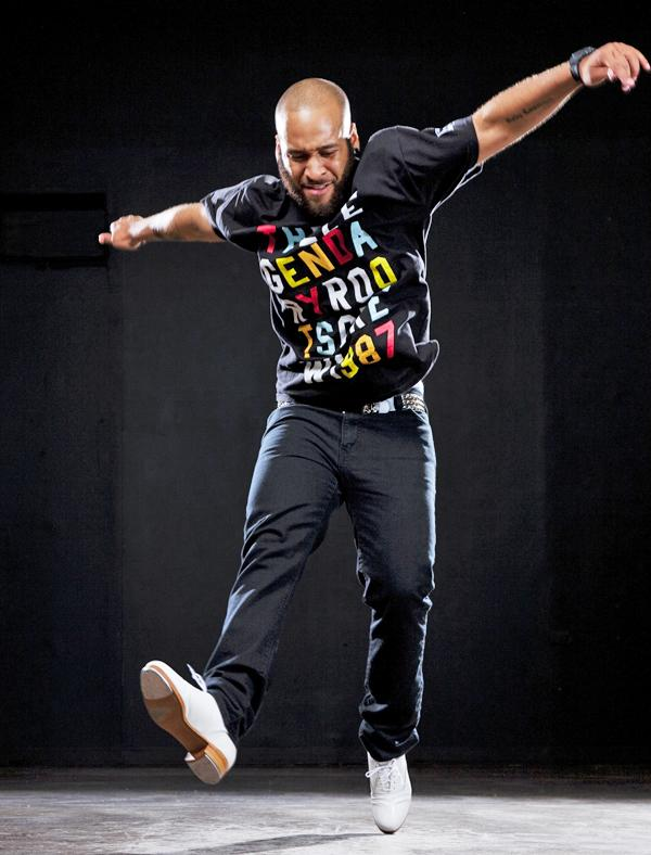 A bald person wearing a mostly black outfit enthusiastically jumps against a black background.