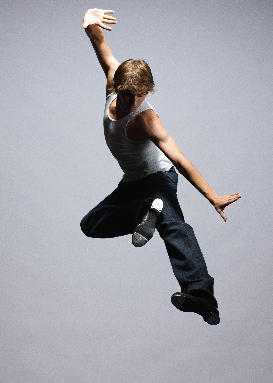 An action photograph captures a performer dancing midair.