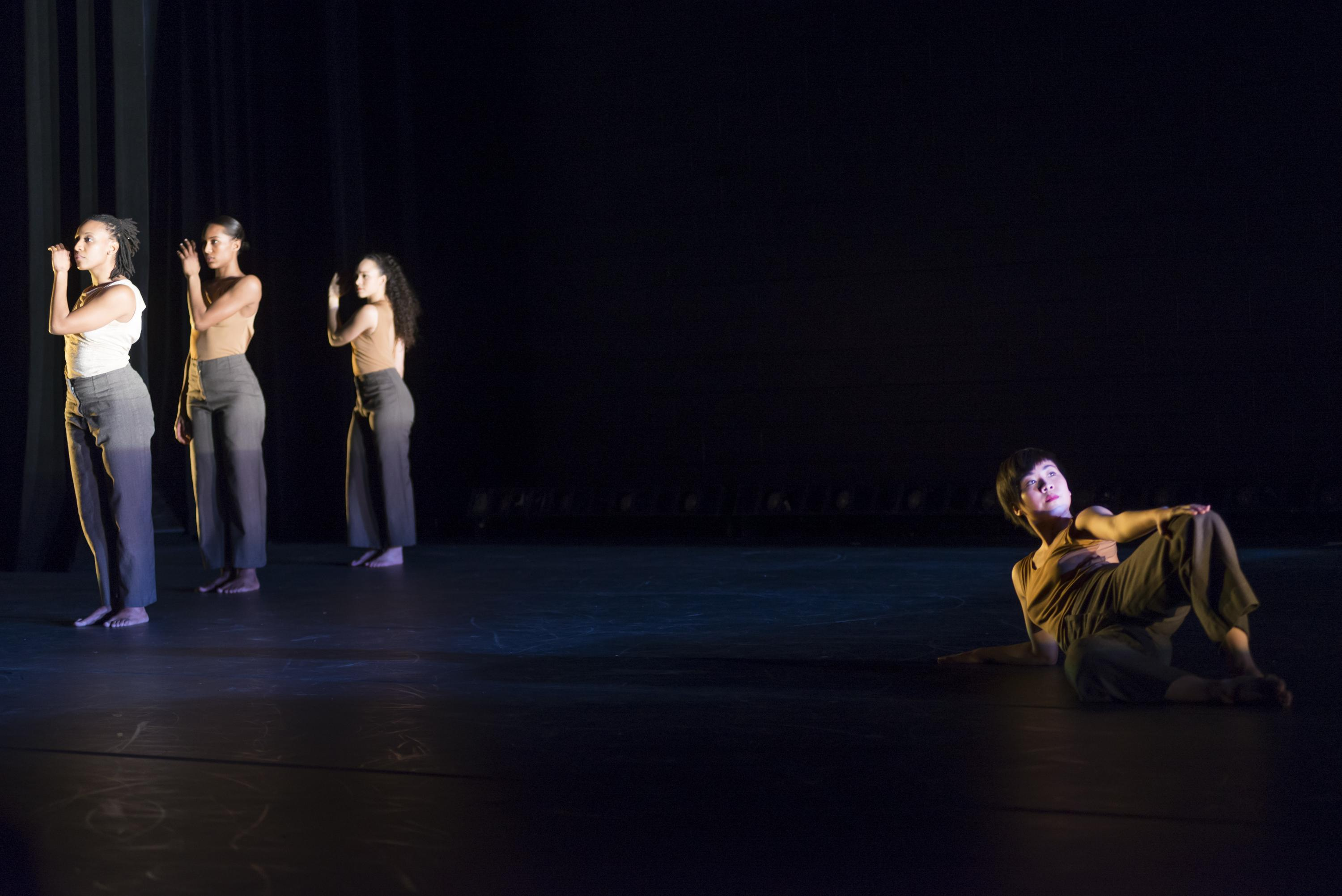 On a dark stage, three women stand in a retreating row on the left and a fourth reclines on the right