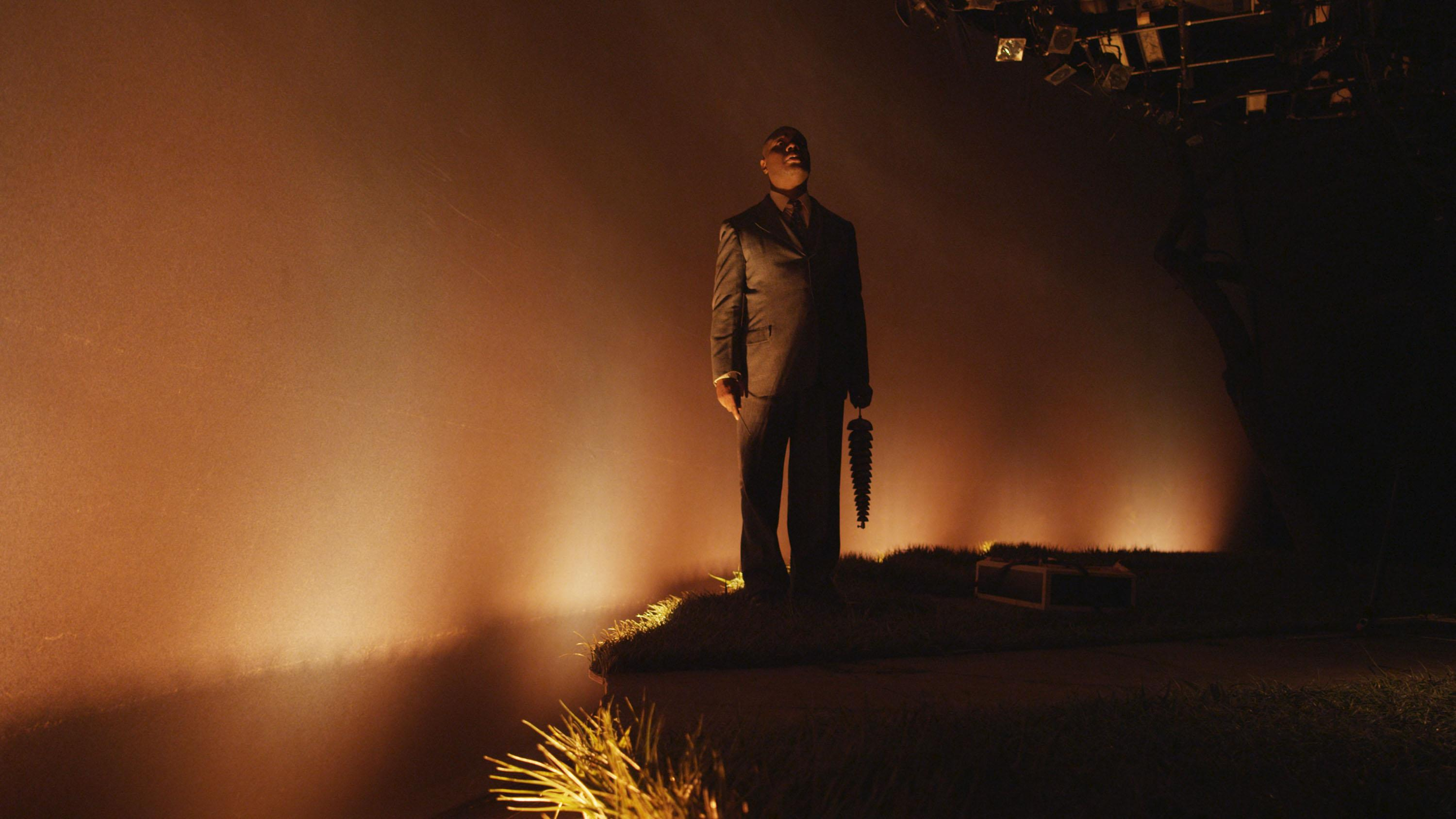 Video still shows a man wearing a suit on an eerie, dimly lit stage.