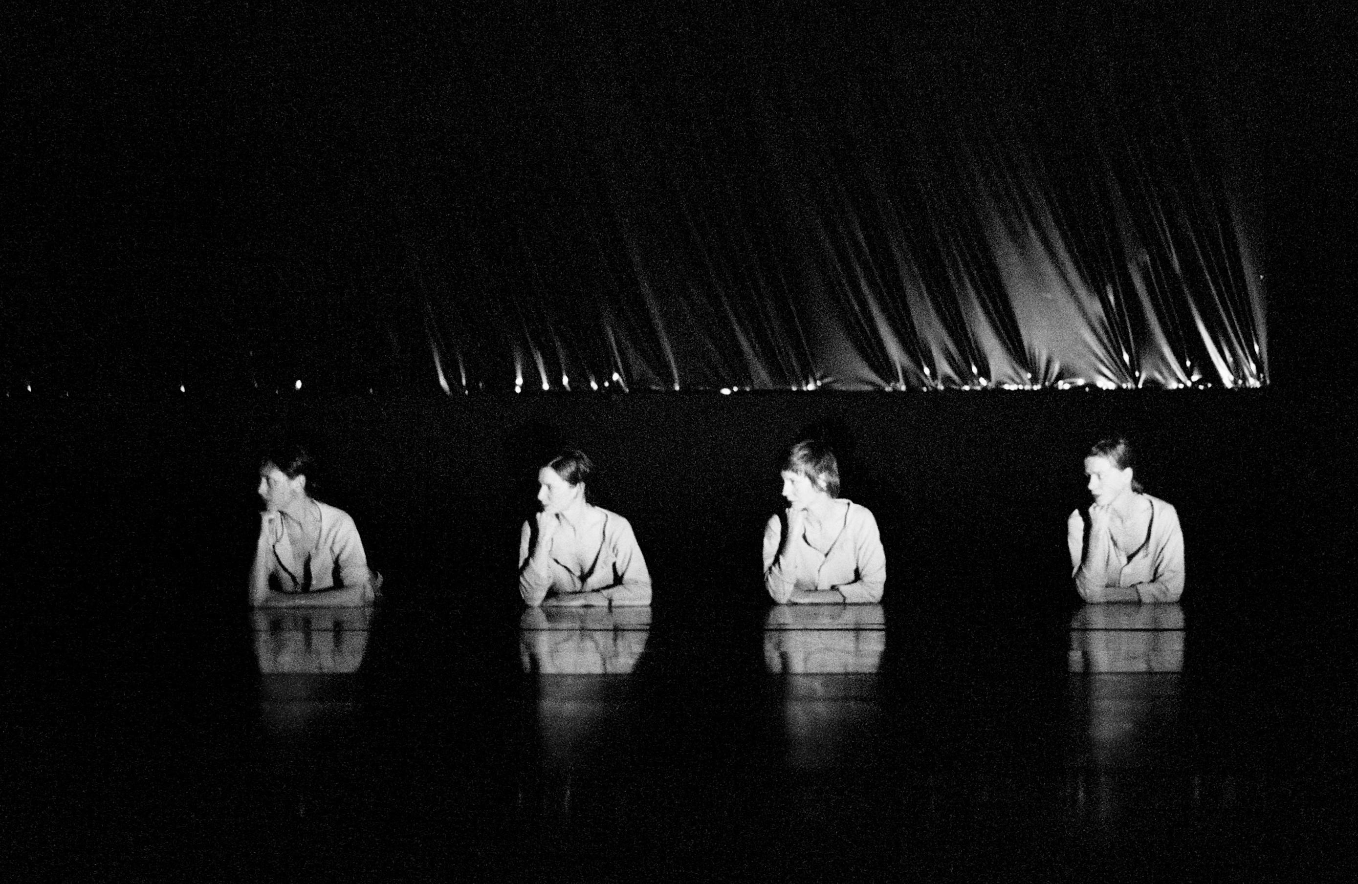Black-and-white performance still of a dark stage with four dancers visible from the waist up, each resting her chin on a hand