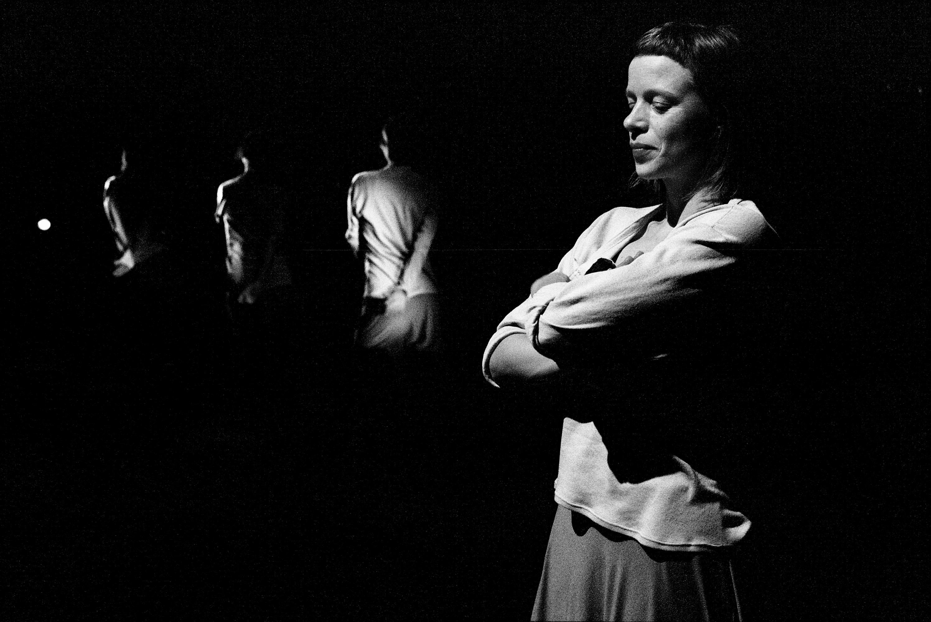 Black-and-white performance still of four dancers progressively disappearing into their pitch-black surroundings