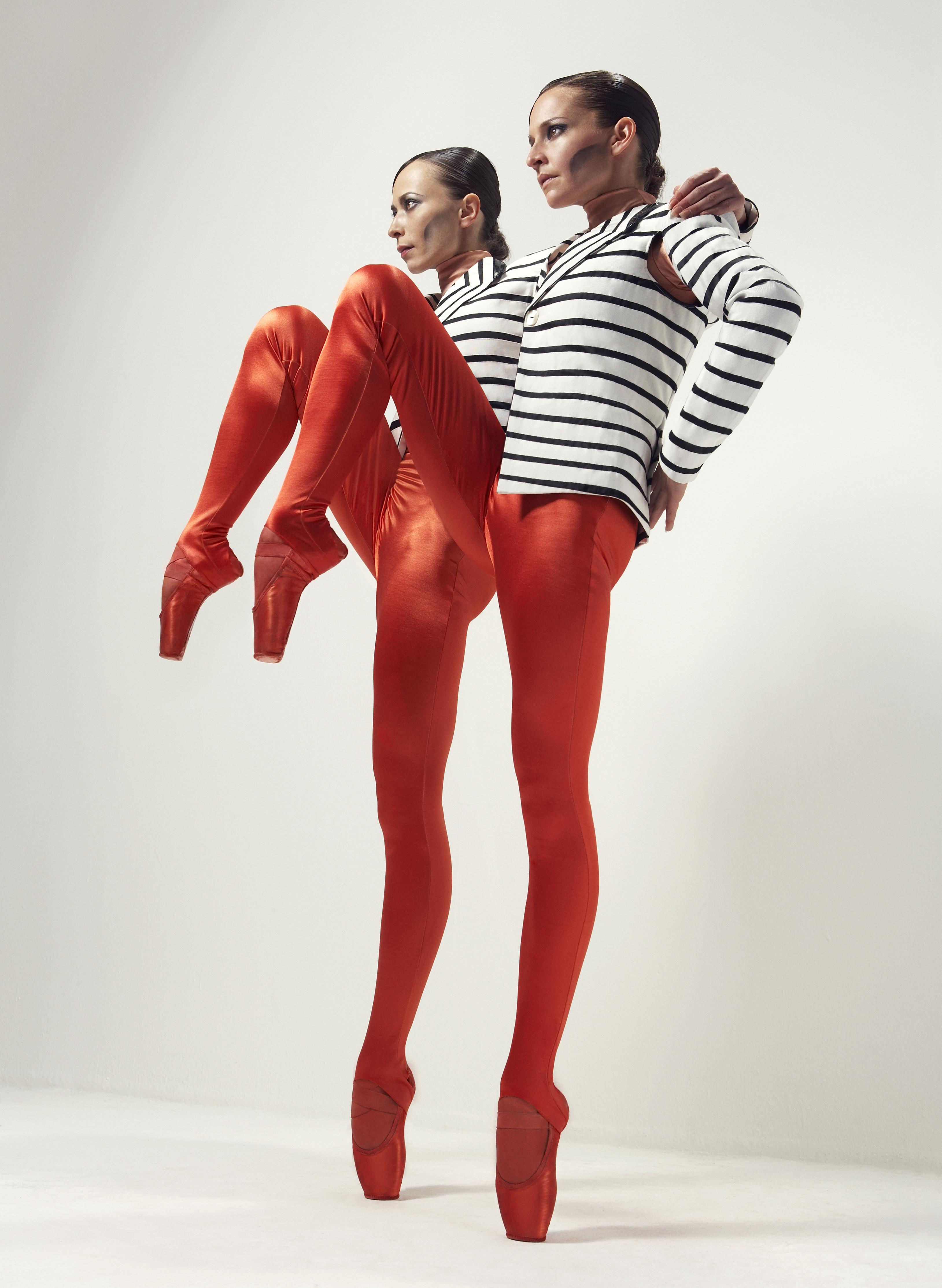 Two identically dressed ballet dancers each stand with one foot on tiptoe and the other leg raised high and bent at the knee.
